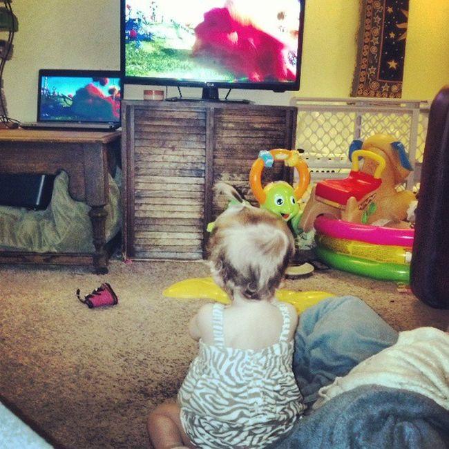 Babygirl watching her Favorite movie Thelorax Cute baby daughter ponytail zebrastripe dress blonde cutiepie happymama