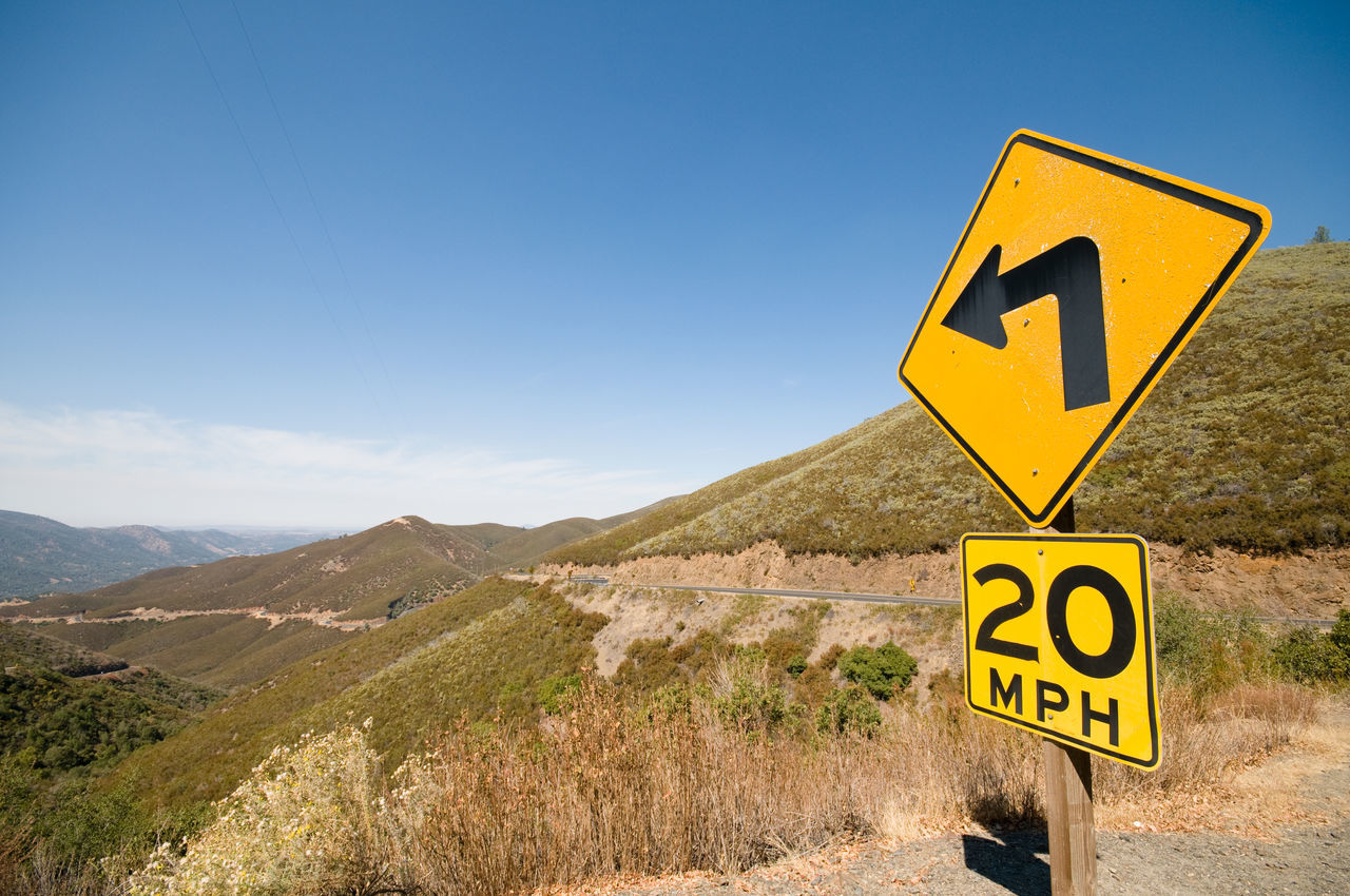 Speed warning sign on a Californian winding road California Communication Day Directional Sign Downhill Road Empty Road Guidance Journey Left Turn Mountain Nature No People Outdoors Road Sign Sky Speed Limit Sign Sunny Day Travel Destinations USA Winding Road Yellow Yellow Sign