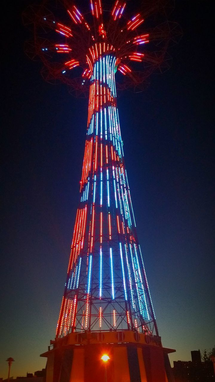 low angle view, amusement park, tower, illuminated, architecture, night, clear sky, built structure, no people, arts culture and entertainment, amusement park ride, red, sky, outdoors, building exterior