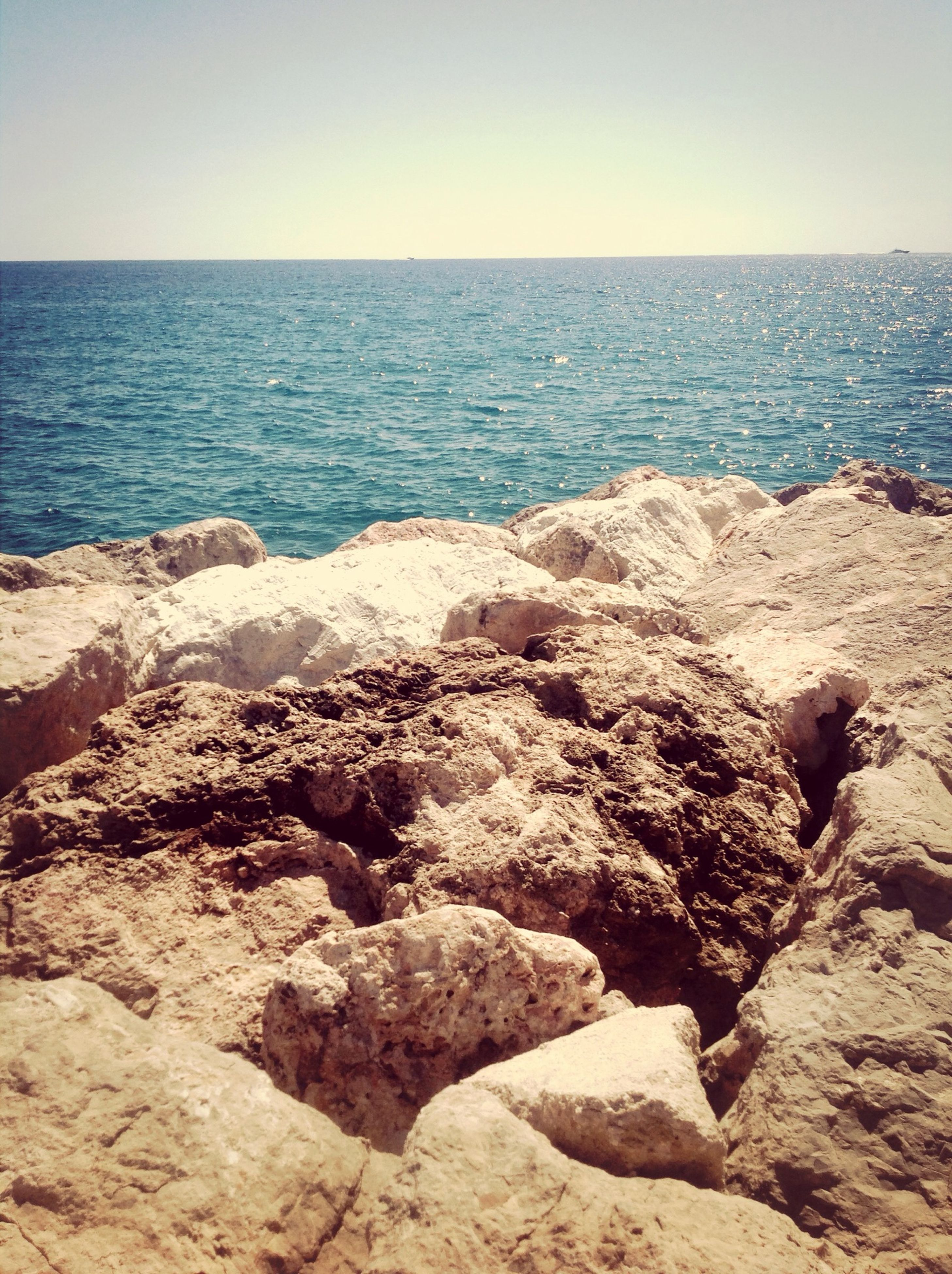 sea, horizon over water, water, scenics, tranquil scene, tranquility, clear sky, beauty in nature, beach, nature, rock - object, shore, idyllic, rock formation, sky, rock, blue, copy space, seascape, remote