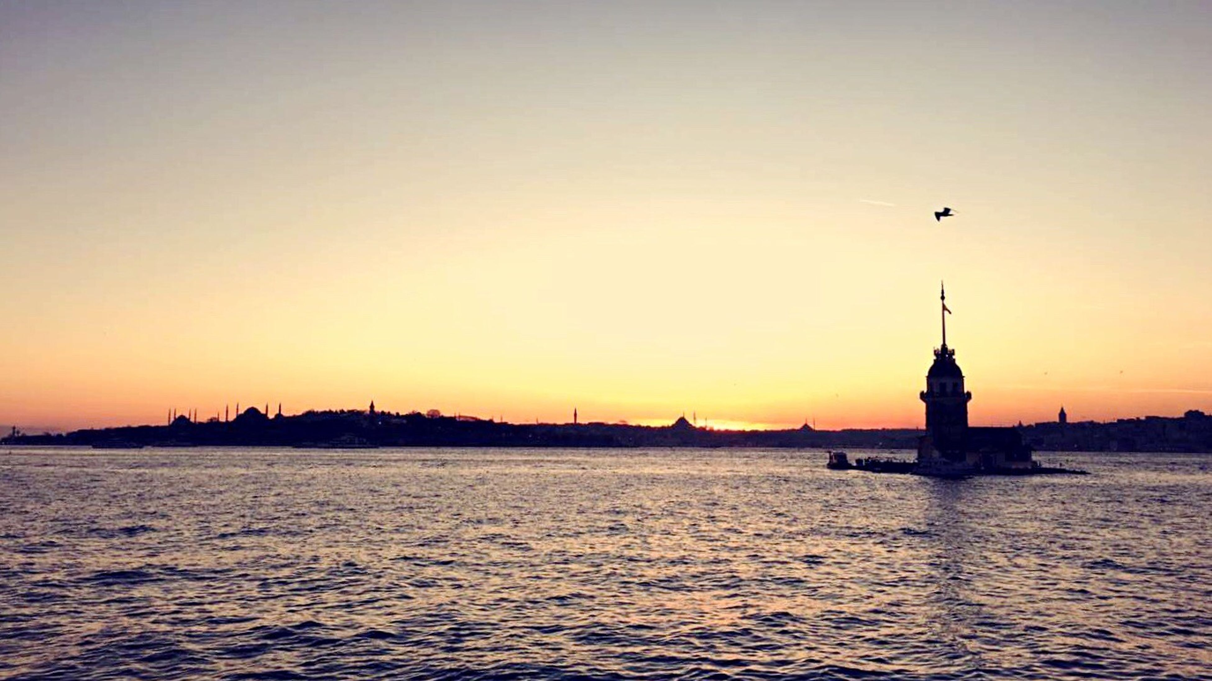 sunset, waterfront, water, building exterior, sea, built structure, architecture, transportation, nautical vessel, rippled, orange color, copy space, boat, mode of transport, clear sky, silhouette, scenics, sky, tranquility, tranquil scene