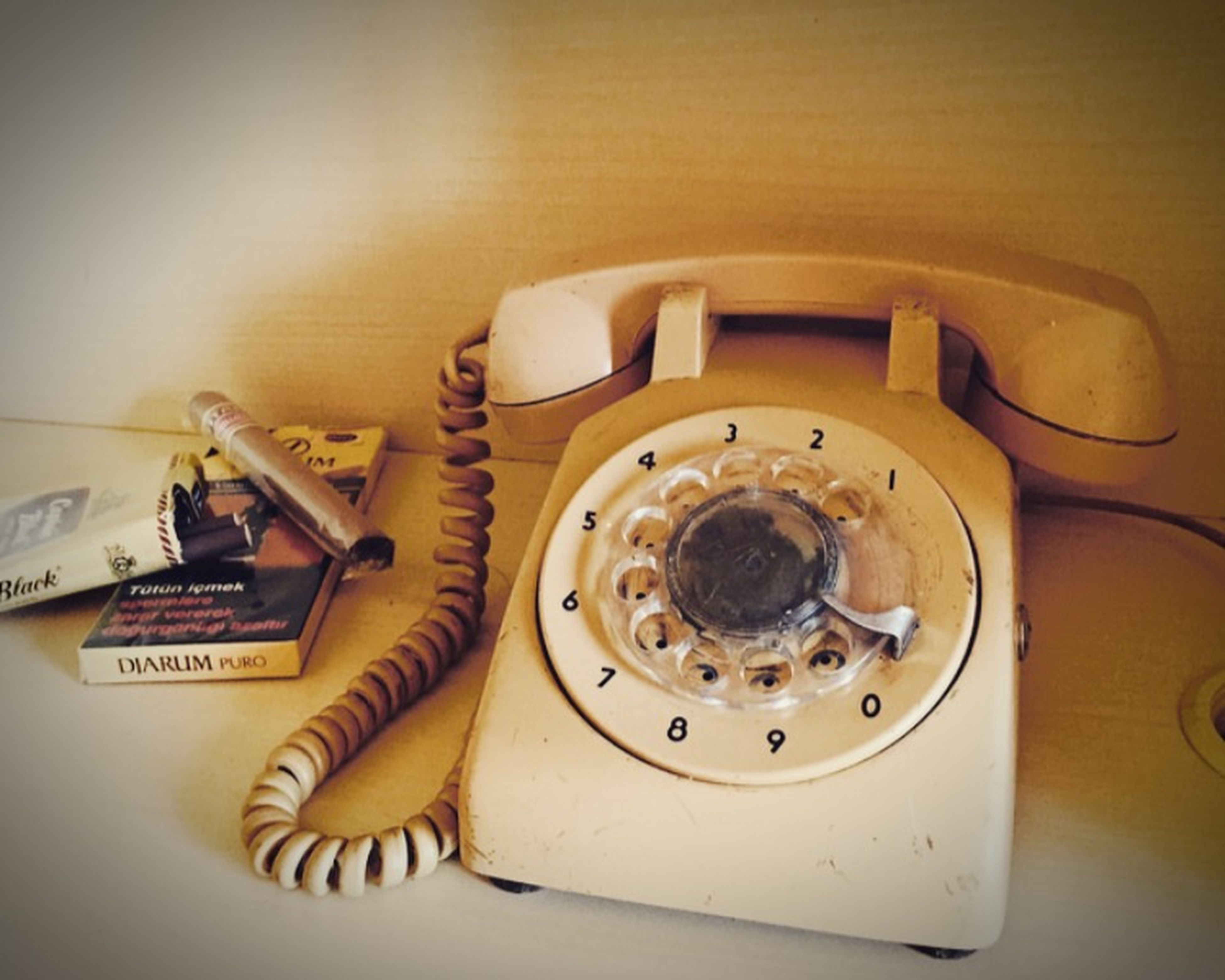 indoors, technology, table, still life, old-fashioned, close-up, high angle view, retro styled, machinery, no people, equipment, communication, home interior, antique, telephone, metal, wood - material, number, white color, connection