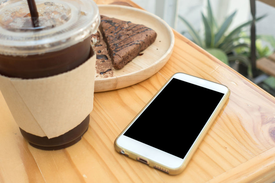 Close-up Coffee - Drink Communication Day Device Screen Digital Tablet Drink Food Food And Drink Freshness High Angle View Indoors  Mobile Phone No People Portable Information Device Smart Phone Sweet Food Table Technology Touch Screen Wireless Technology