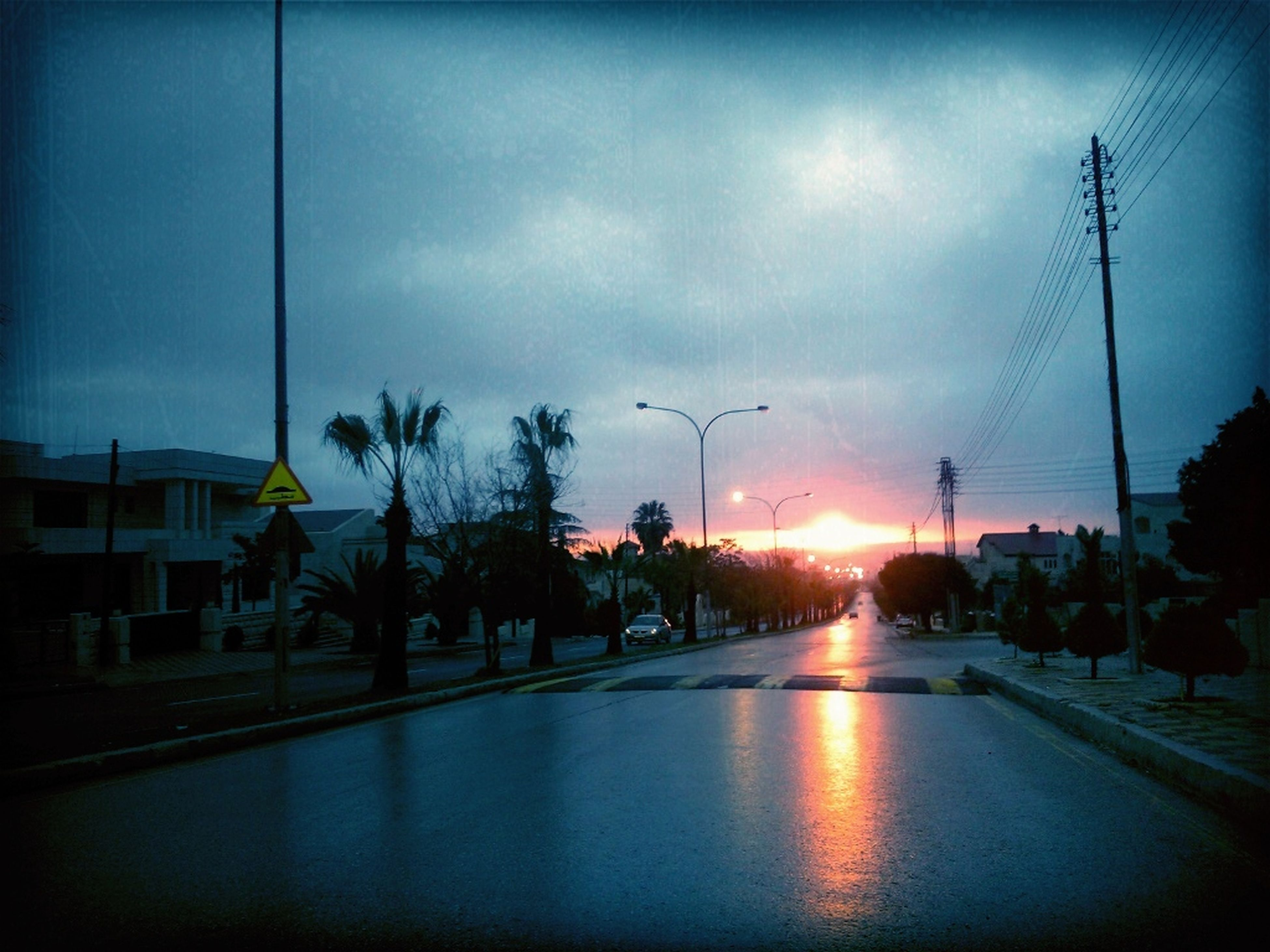 sunset, sky, building exterior, silhouette, built structure, street light, cloud - sky, street, architecture, transportation, road, sun, power line, car, cloud, city, sunlight, outdoors, tree, electricity pylon