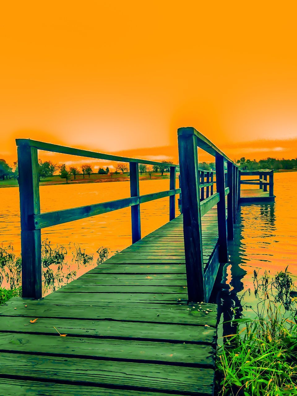 nature, sunset, tranquil scene, outdoors, scenics, beauty in nature, tranquility, no people, water, wood - material, built structure, bridge - man made structure, grass, wood paneling, sunlight, sky, wooden post, day, architecture, sea, clear sky