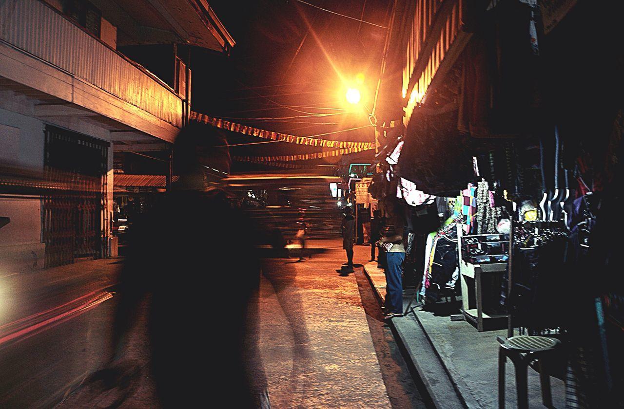Blurred Image Of Man Walking On Street At Night
