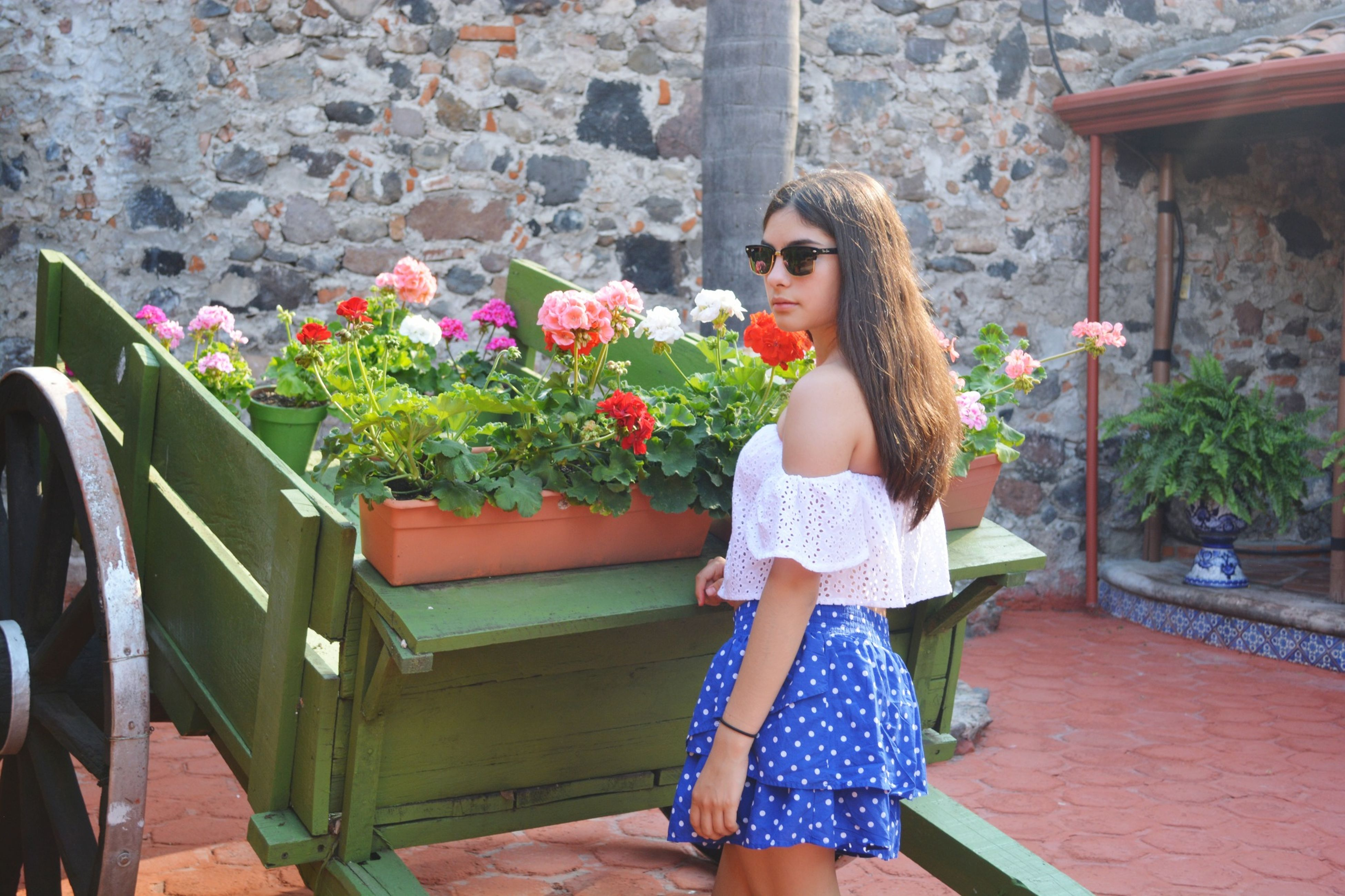 flower, casual clothing, lifestyles, building exterior, full length, built structure, standing, architecture, person, leisure activity, young adult, holding, young women, front view, potted plant, wall - building feature, plant, day