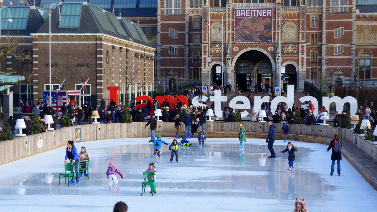 ice rink, large group of people, real people, winter sport, leisure activity, lifestyles, ice-skating, ice hockey, sport, architecture, built structure, day, cold temperature, winter, building exterior, playing, outdoors, hockey, water, people, adult