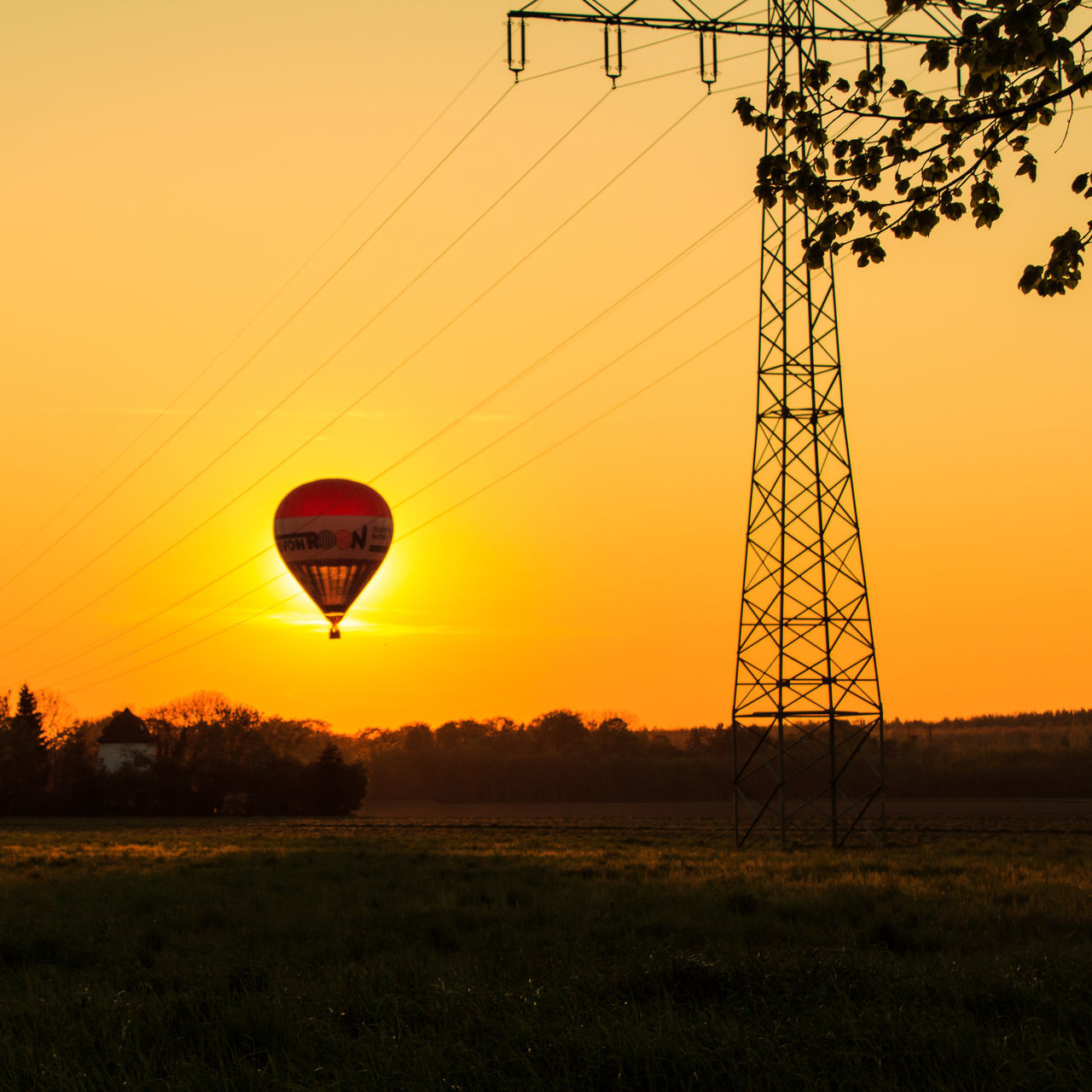 sunset, hot air balloon, field, sky, silhouette, electricity pylon, nature, tree, clear sky, outdoors, landscape, beauty in nature, no people, grass, day