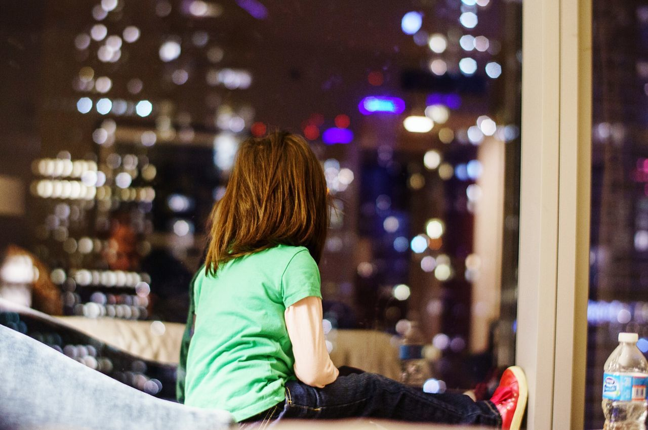 Rear View Of Girl Looking Through Glass Window At Night