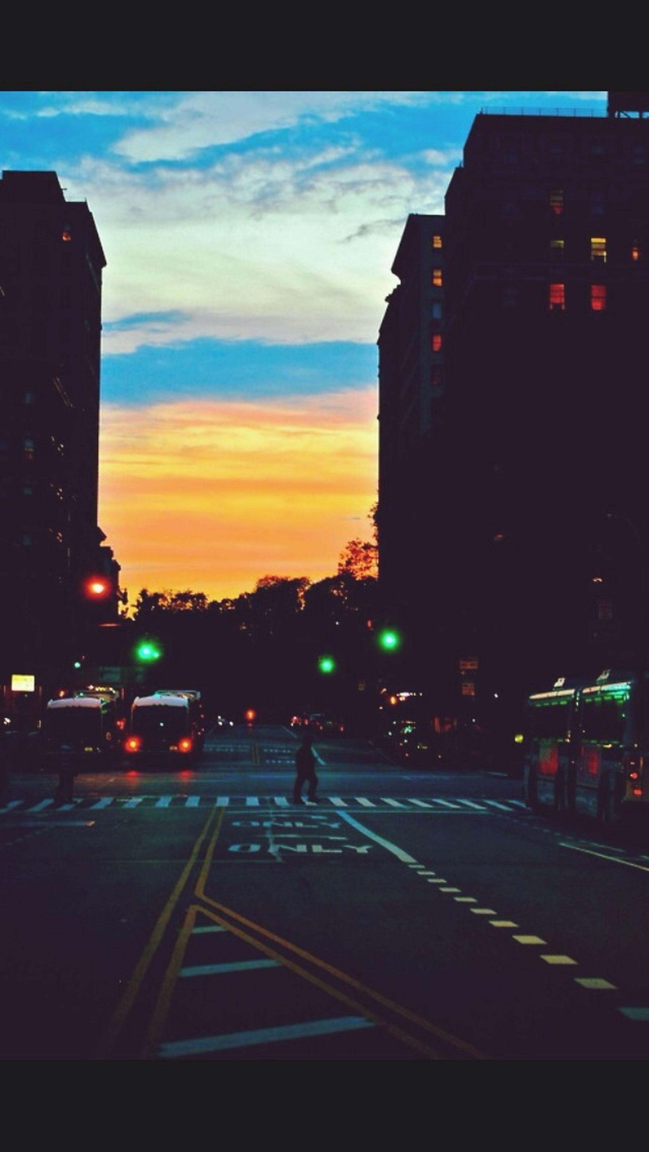 building exterior, architecture, built structure, illuminated, transportation, city, street, sky, road, dusk, sunset, car, night, street light, land vehicle, city street, road marking, city life, silhouette, building