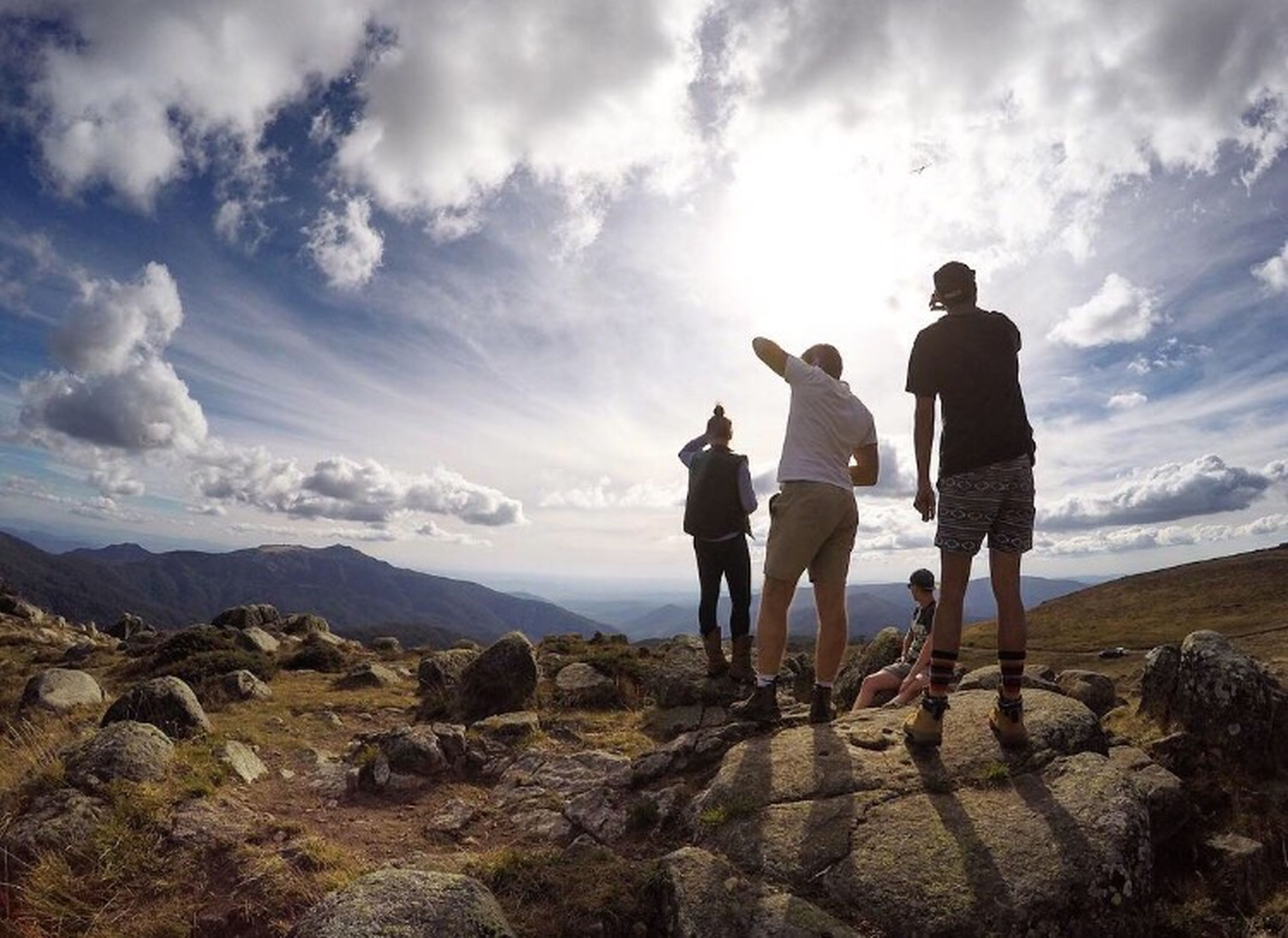 sky, men, lifestyles, rock - object, leisure activity, cloud - sky, togetherness, standing, full length, person, nature, landscape, scenics, rear view, tranquility, beauty in nature, rock formation, tranquil scene, mountain