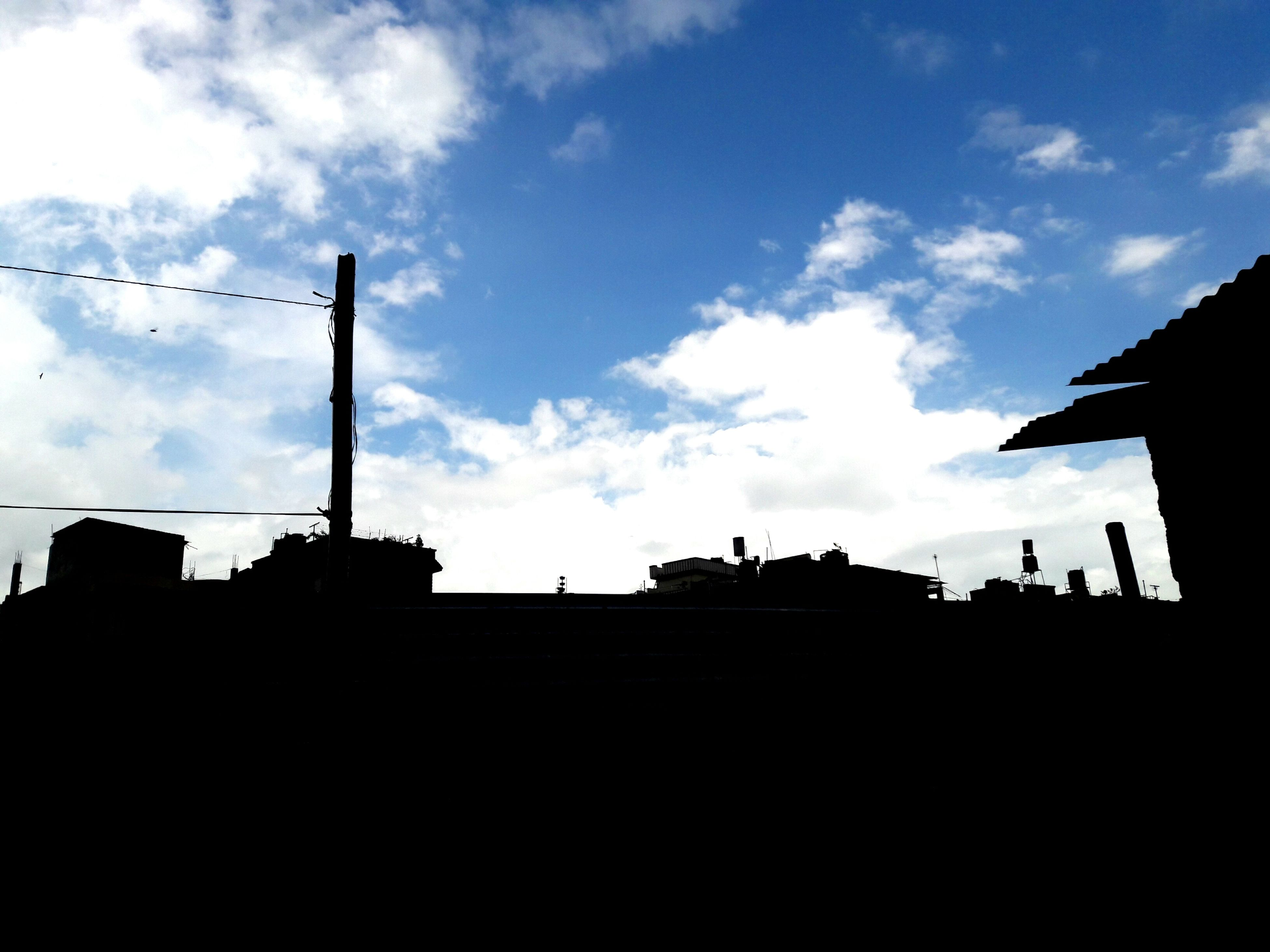 building exterior, architecture, built structure, sky, low angle view, cloud - sky, cloud, building, cloudy, outdoors, high section, day, no people, blue, nature, dark