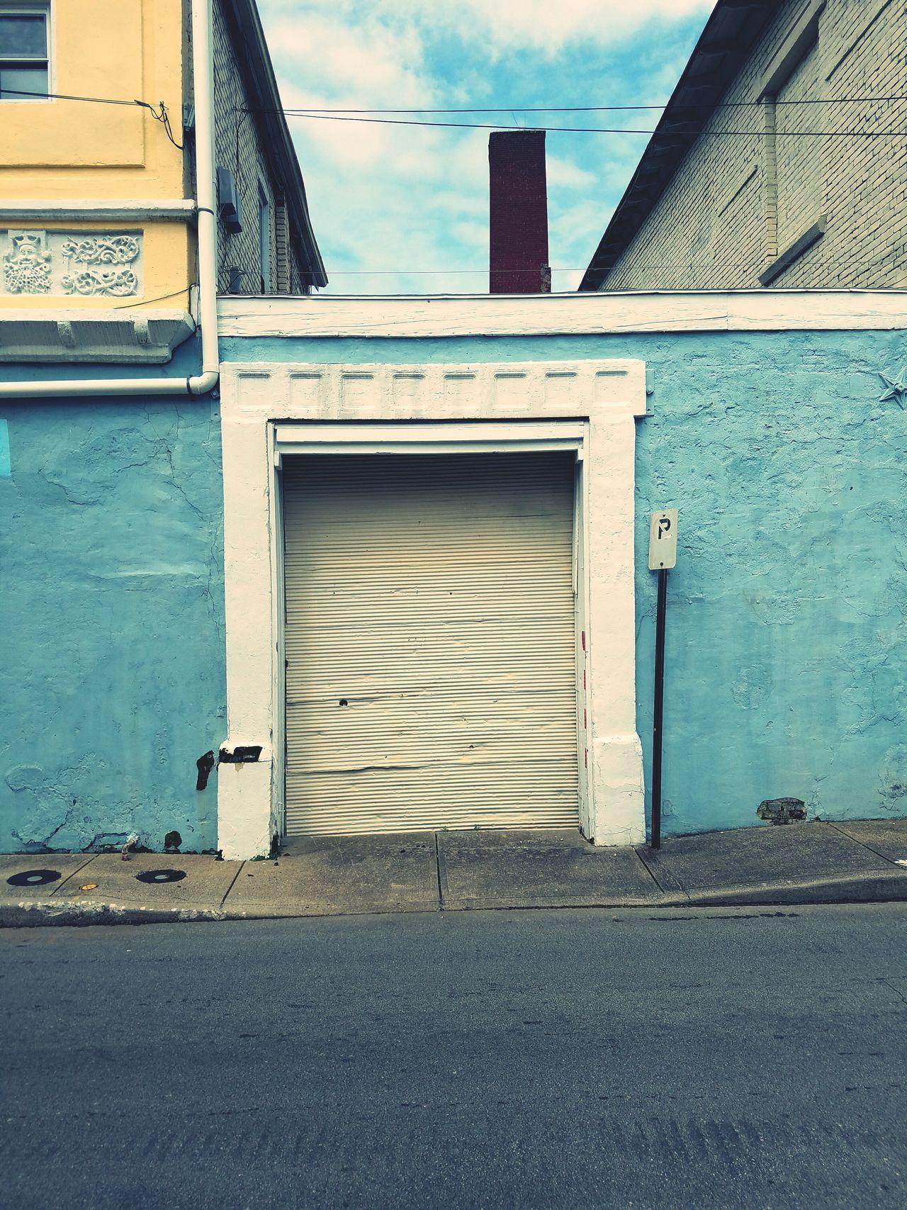 Garage Door Metal Door Sidewalk Photograhy Street Photography Streetphoto_color Old Buildings Oldschool Intricatedetails Yellow BuildingBlue Building Blue Building Blue Sky Blue Sky Clouds And Sky Chimneys Downtown