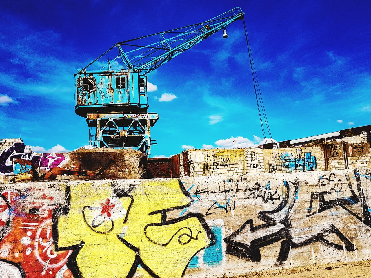 graffiti, cloud - sky, sky, art and craft, architecture, built structure, outdoors, day, building exterior, communication, sunlight, blue, low angle view, no people