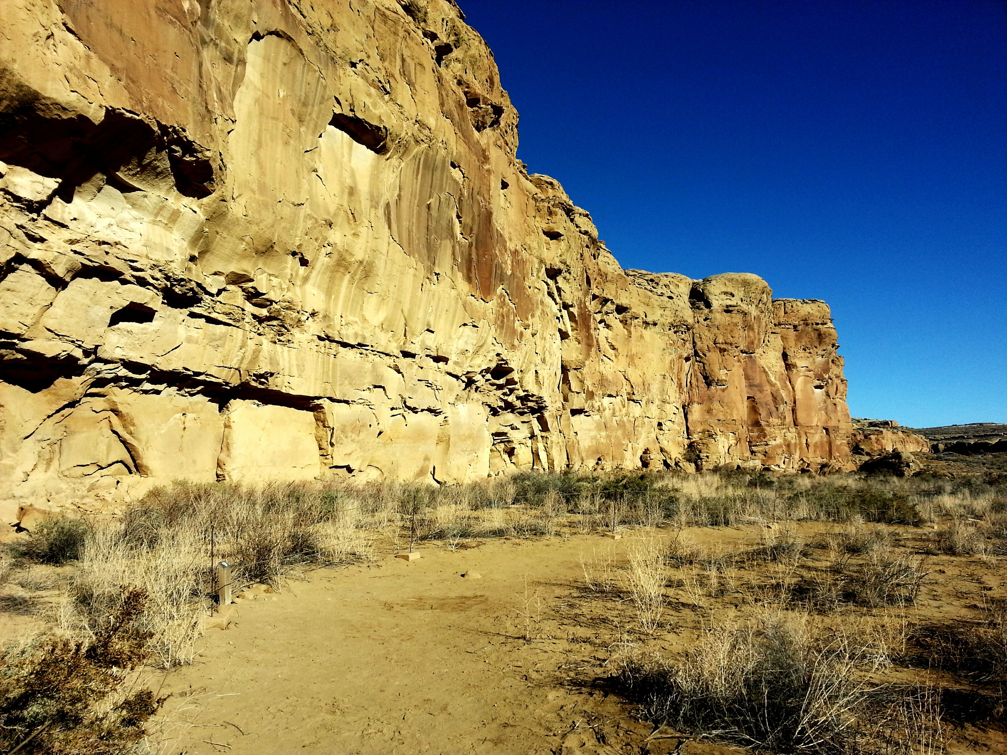 clear sky, blue, rock formation, tranquility, nature, tranquil scene, rock - object, copy space, sunlight, beauty in nature, scenics, sand, landscape, day, non-urban scene, sky, geology, outdoors, low angle view, no people