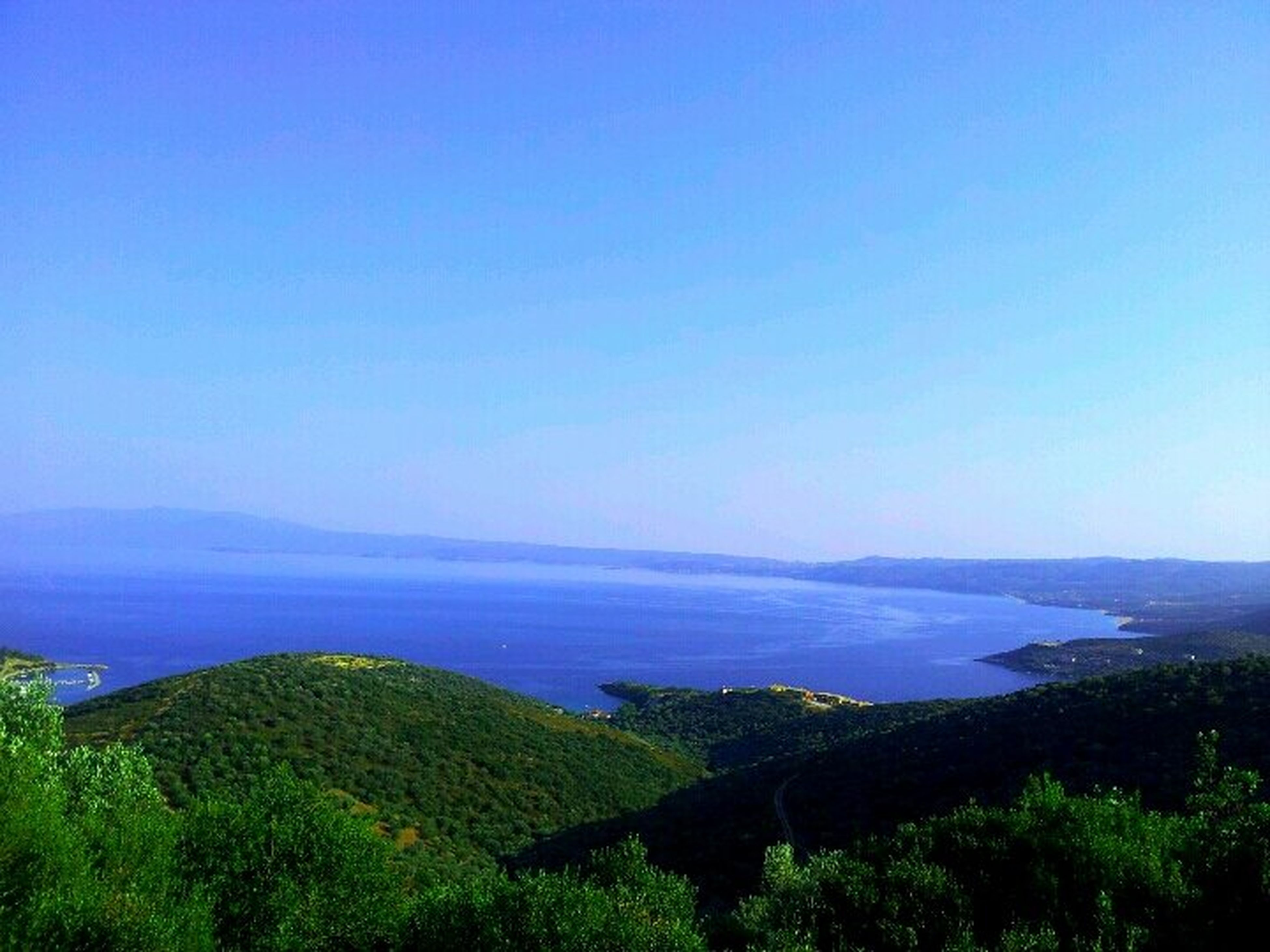 tranquil scene, blue, scenics, sea, tranquility, copy space, clear sky, beauty in nature, water, horizon over water, nature, landscape, idyllic, high angle view, mountain, coastline, tree, non-urban scene, grass, sky