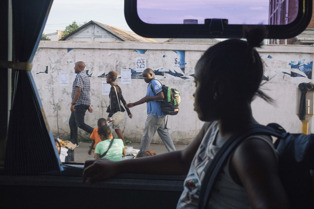 A Zimbabwean girl traveling from South Africa back home to start school in January 2016, peers out of the window of our overnight bus as it arrives in Zimbabwe's capital city Harare . The Drive Women Lifestyles Tourist Tourism Real People Travel Destinations Outdoors Bus Bus Interior Vehicle Interior Africa Commerce