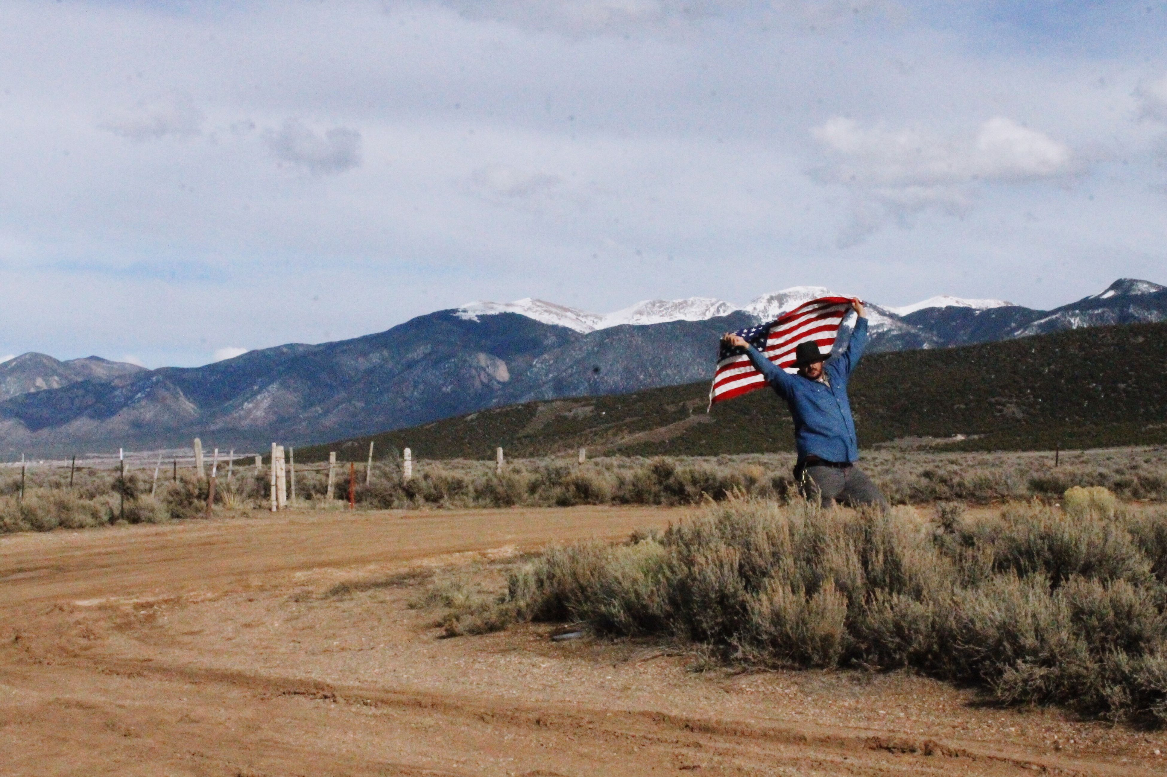 flag, mountain, patriotism, one person, full length, outdoors, sky, people, landscape, nature, wilderness area, adult, young adult, day, adults only
