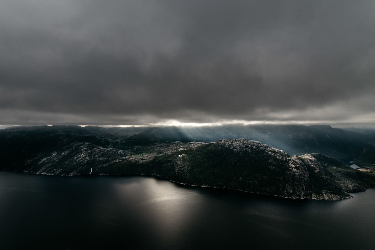 It was not my first time in Norway, but every time someone speaks about the viking country, it's this day that pops into my head. We got up early; crawled out of our tent while the stars were still covering the sky. A few hours hike to our destination: Preikestolen. One of Norway's great landmarks - and one that stayed in my soul since then. The morning raised and by the time we reached the plateau, the sun was already some minutes above the mountain range, covered behind a thick coat of clouds. Wind was pushing the low hanging grey into the land. A theatre like, rays of light were illuminating parts of the landscape from time to time to catch our attention. Mountains as far as the eye can see, only interrupted by the fjord, 600m below our feet. Beauty In Nature Clouds Day Fjord Landmark Landscape Mountain Mountain Range Nature No People Norway Outdoors Preikestolen Scenery Scenics Sky Water Waterfront