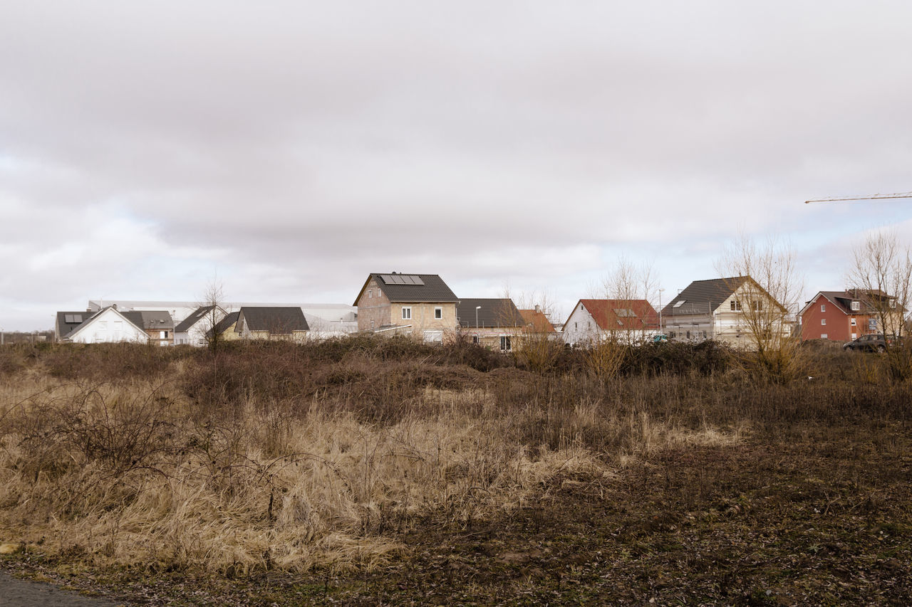 HOUSES ON GRASSY FIELD AGAINST CLOUDY SKY