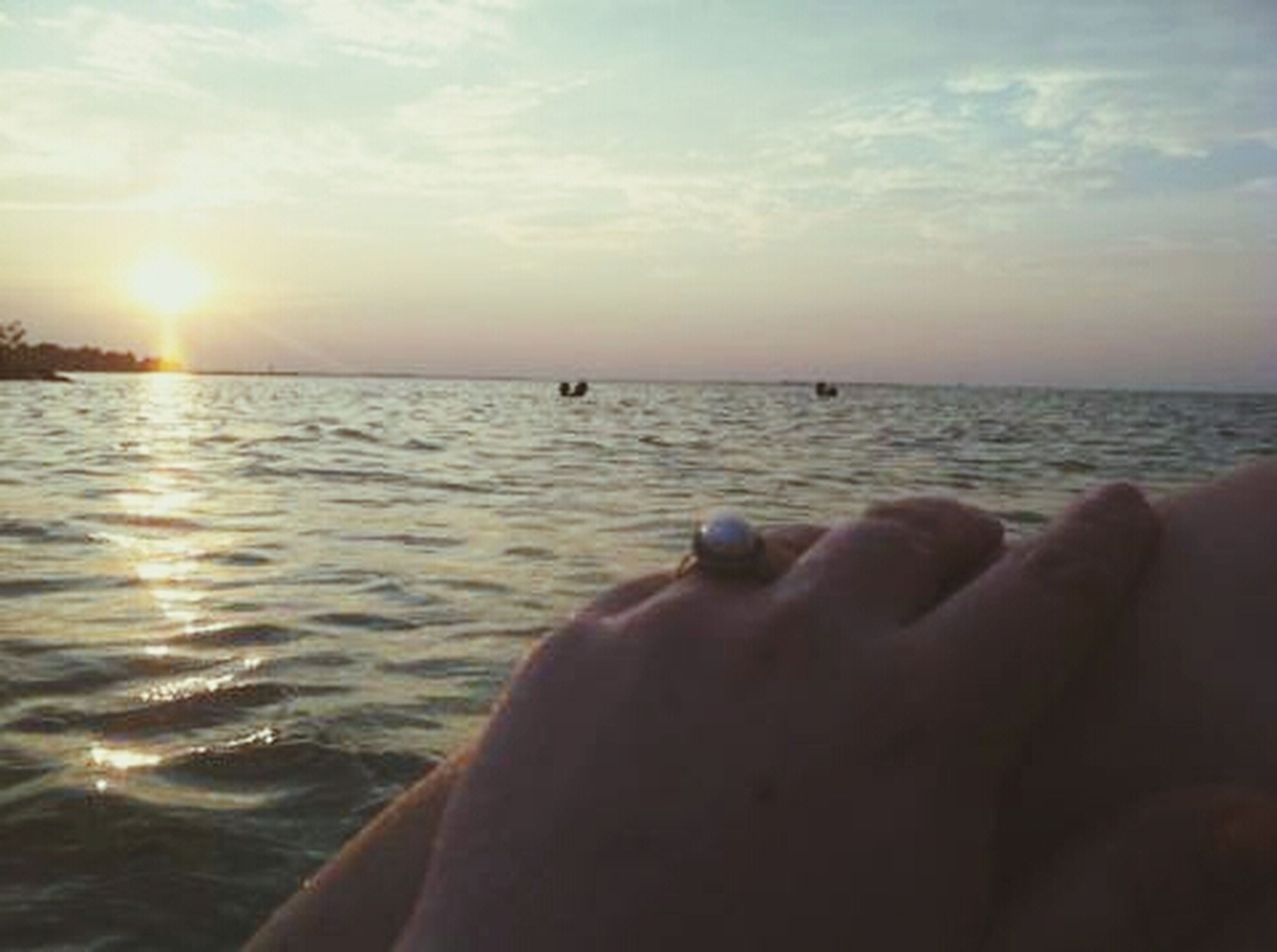 water, sea, horizon over water, sky, person, sunset, part of, unrecognizable person, personal perspective, sun, lifestyles, leisure activity, scenics, cropped, beauty in nature, sunlight, nature