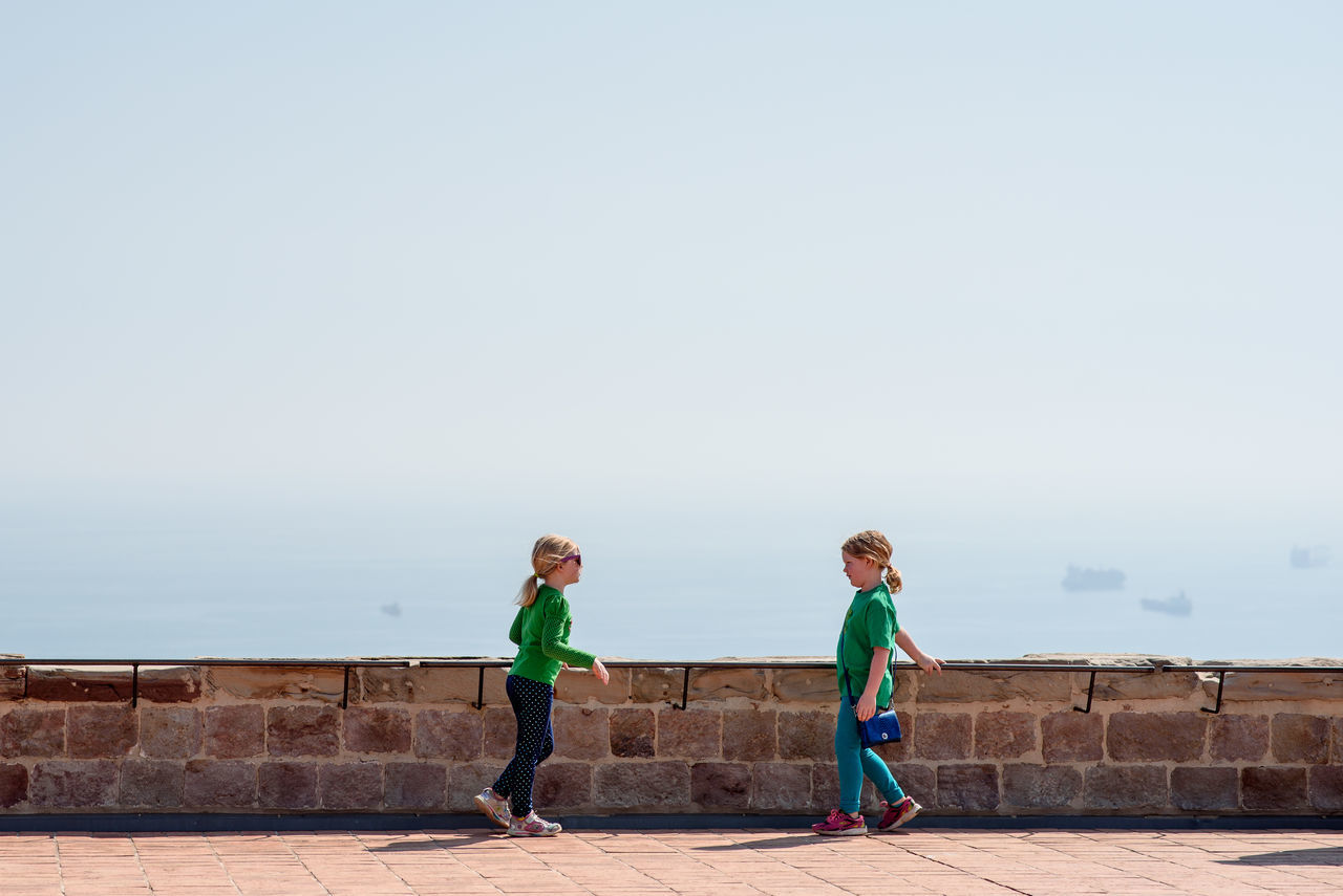 full length, two people, day, copy space, clear sky, outdoors, real people, standing, sky, childhood, sea, togetherness, nature, horizon over water, retaining wall, lifestyles, boys, friendship, water, architecture, beauty in nature, people