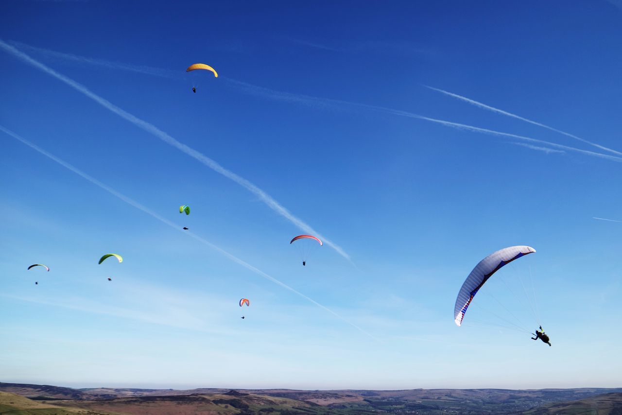 adventure, extreme sports, parachute, mid-air, leisure activity, flying, sport, nature, blue, outdoors, real people, day, low angle view, paragliding, scenics, beauty in nature, kite - toy, sky, lifestyles, multi colored, vapor trail