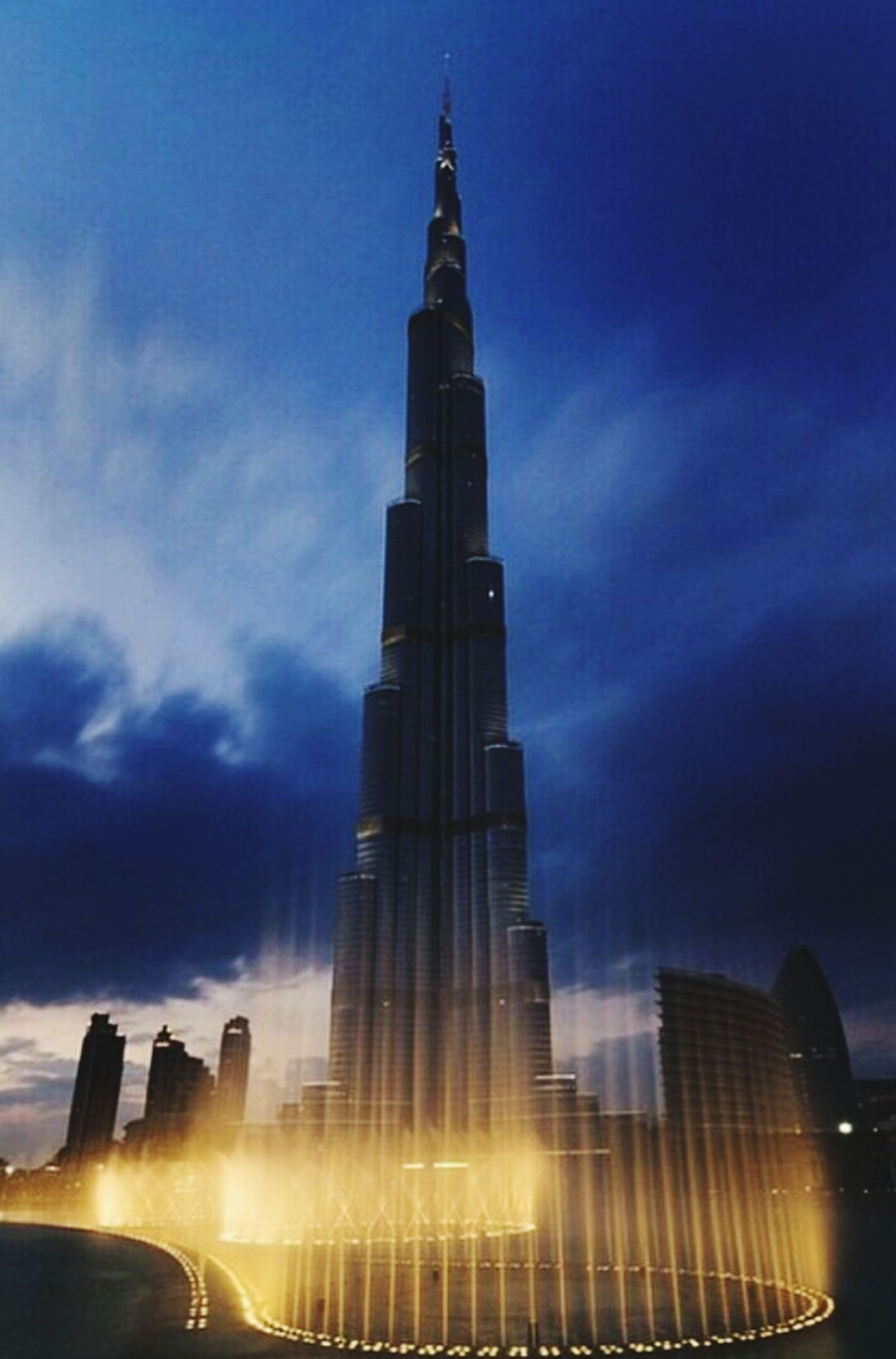 sky, architecture, tower, night, low angle view, built structure, outdoors, no people, skyscraper, illuminated