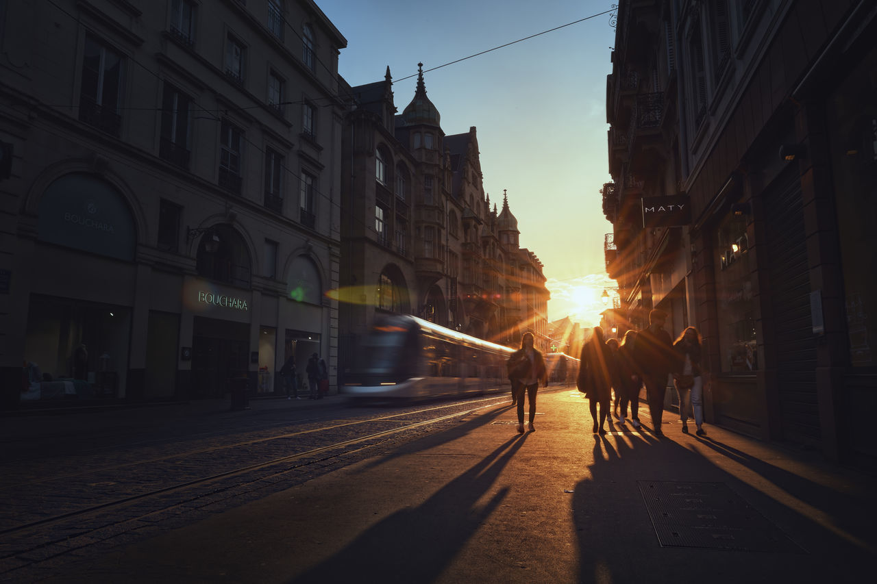 building exterior, architecture, built structure, city, street, transportation, outdoors, real people, sunlight, sunset, men, sky, day, people