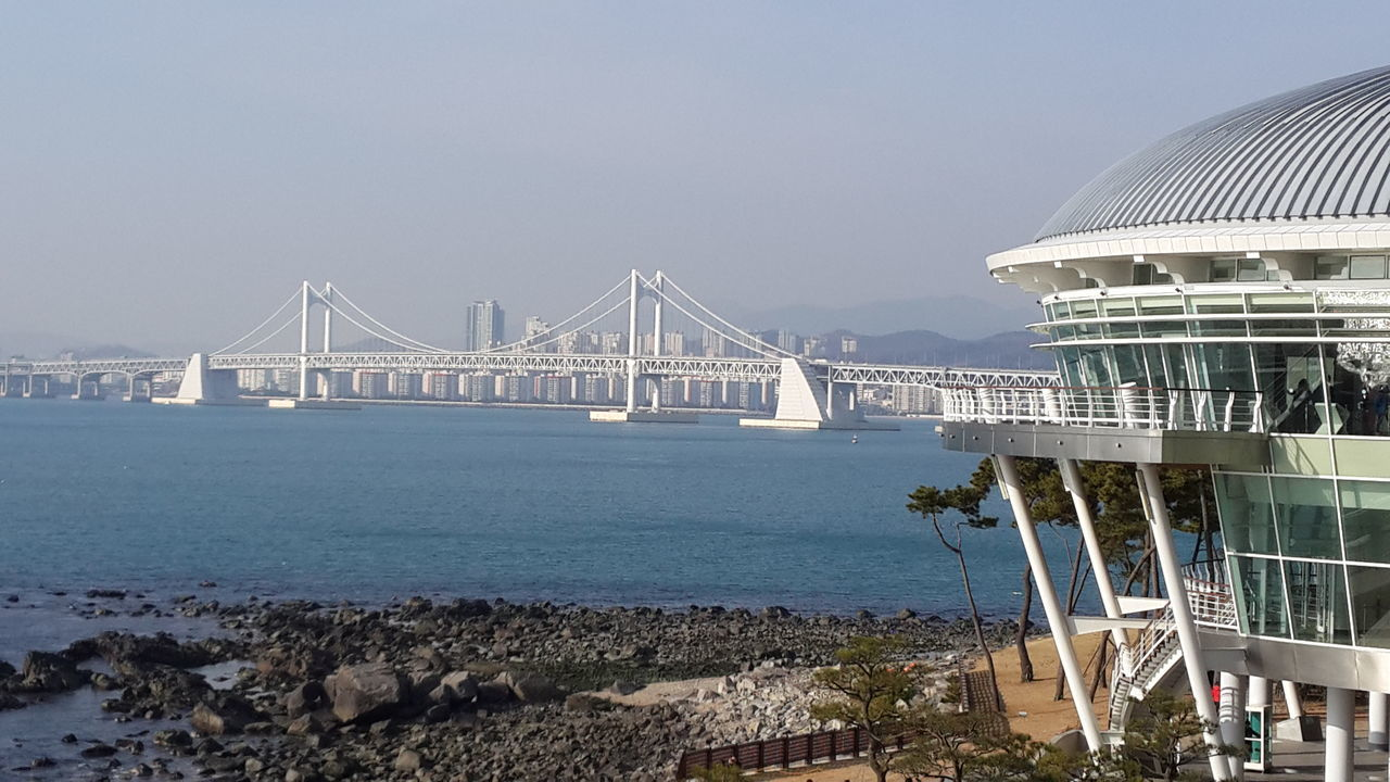 architecture, built structure, water, bridge - man made structure, connection, travel destinations, building exterior, outdoors, travel, sea, transportation, day, sky, no people, clear sky, suspension bridge, nature, city