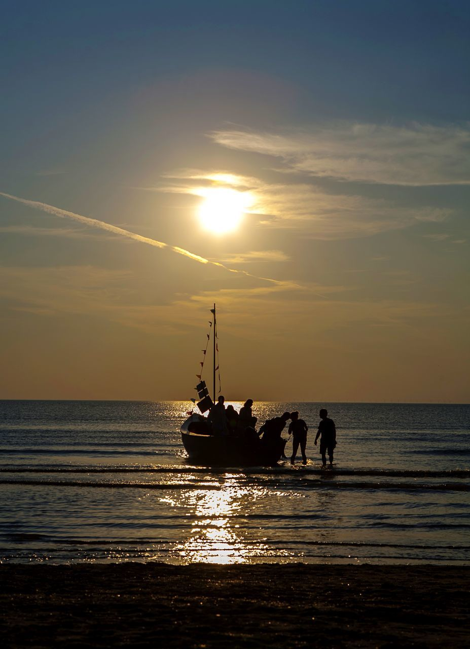 Silhouette People On Boat Moored In Sea At Sunset