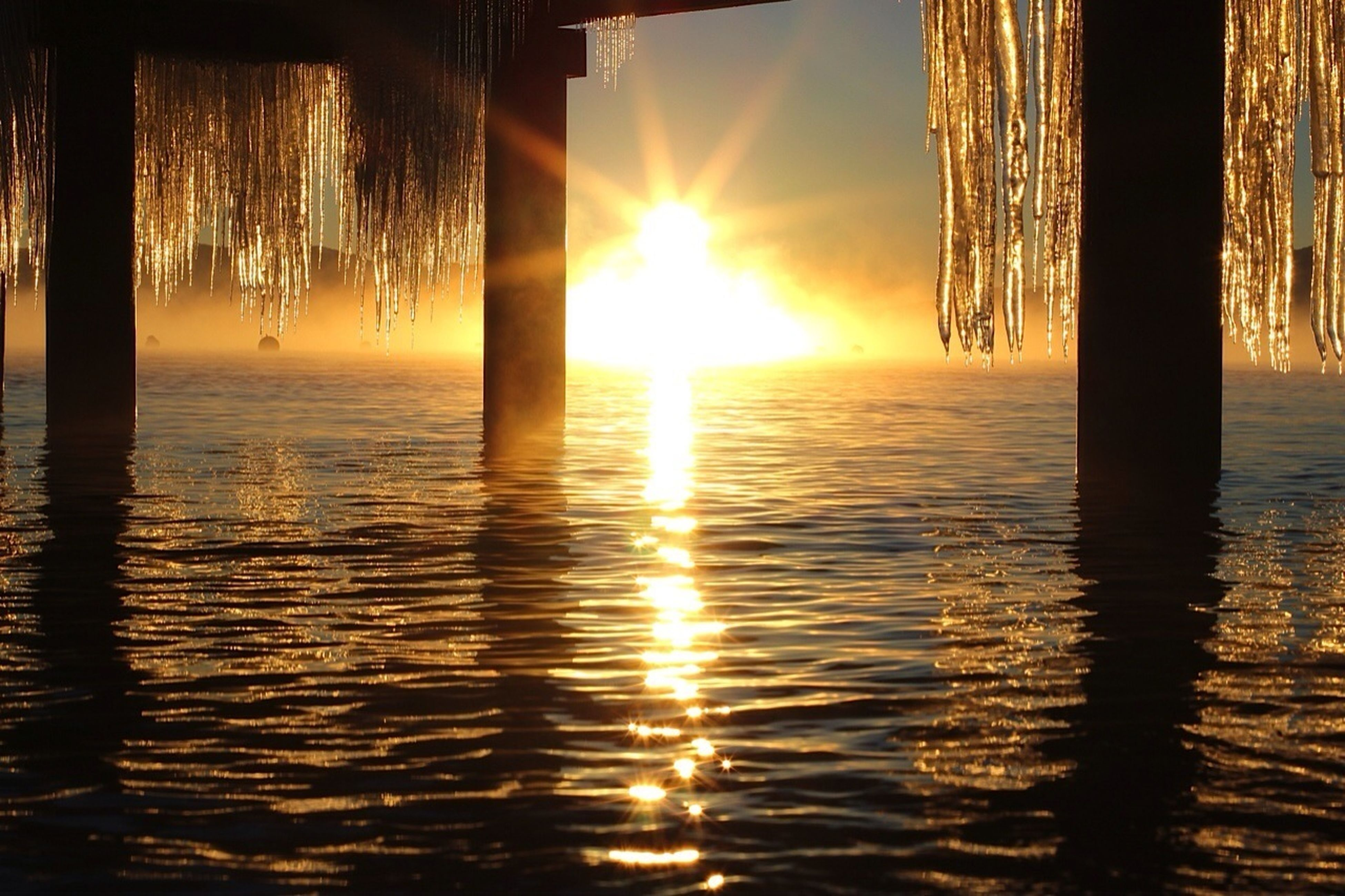 sunset, water, sun, reflection, waterfront, sunlight, orange color, silhouette, tranquility, rippled, nature, tranquil scene, sea, beauty in nature, lake, scenics, built structure, sky, sunbeam, architecture