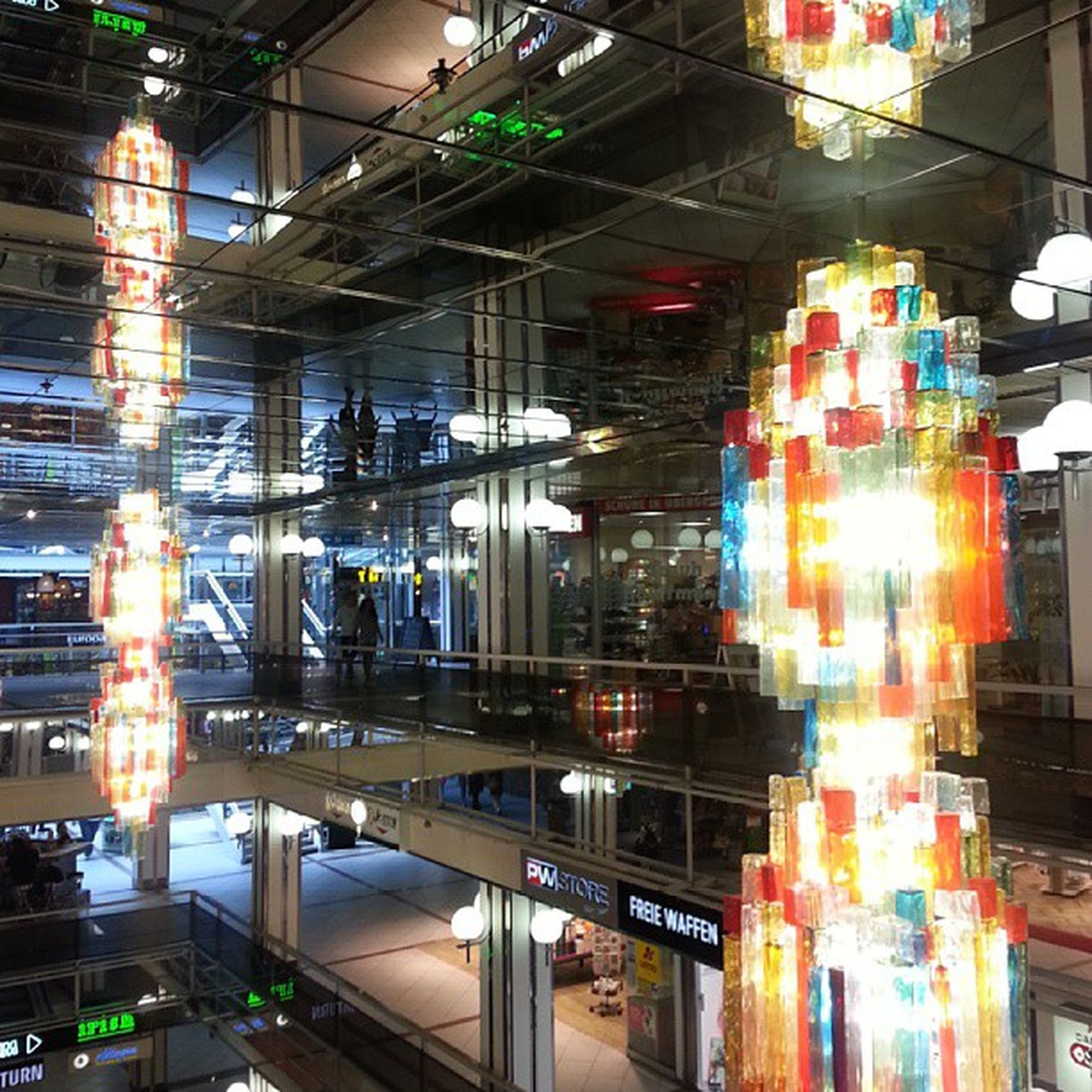 illuminated, architecture, built structure, night, lighting equipment, building exterior, city, reflection, indoors, modern, glass - material, store, incidental people, light - natural phenomenon, no people, city life, low angle view, glowing, multi colored, building