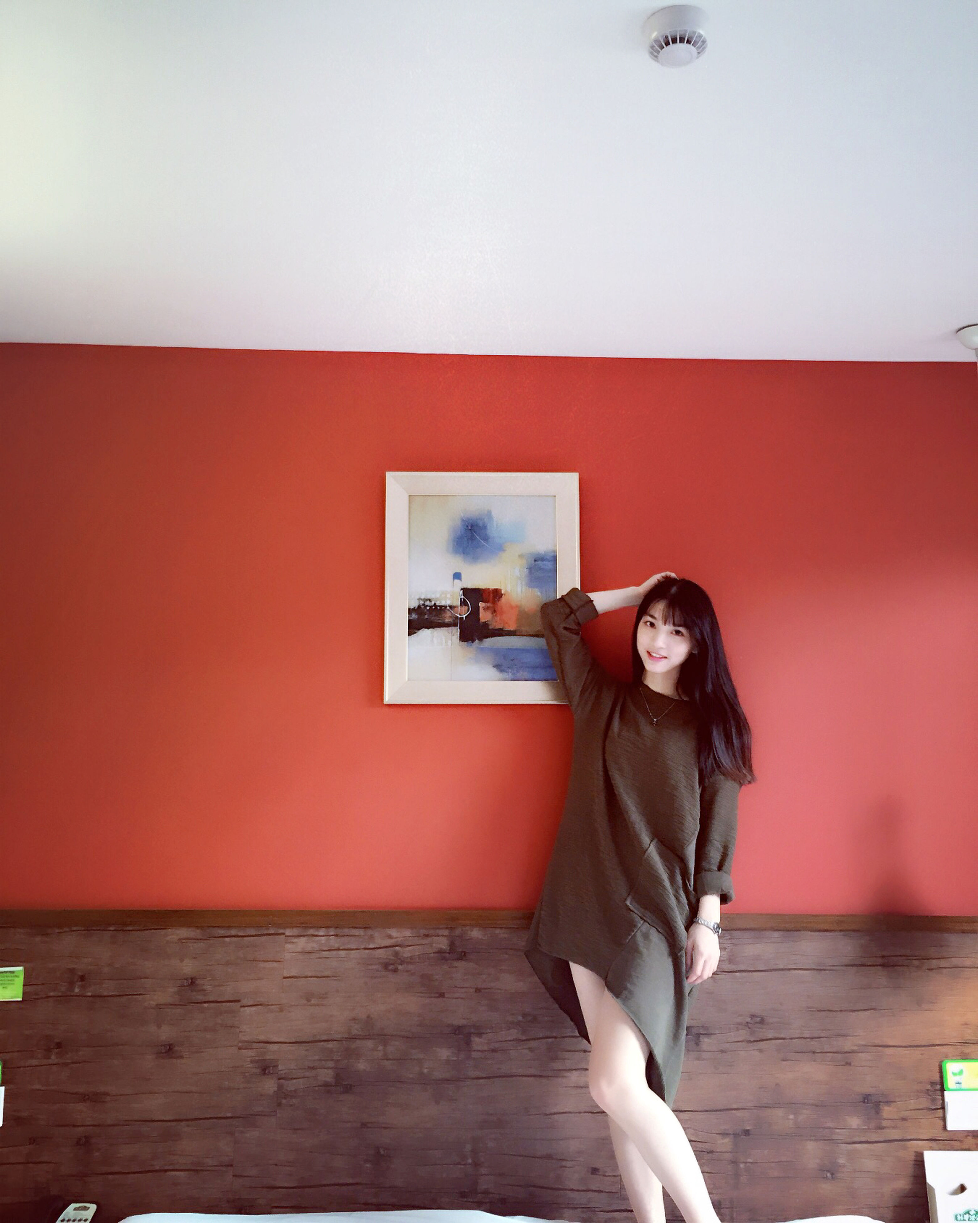 full length, casual clothing, lifestyles, indoors, wood - material, wall - building feature, standing, sitting, copy space, leisure activity, red, wall, young adult, built structure, door, rear view, holding, side view