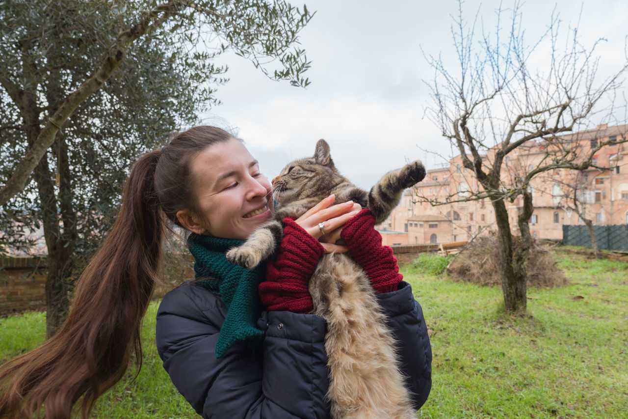 Adult Carefree Cat Cheerful Cold Temperature Day Domestic Animals Domestic Cat Friendly Fun Happiness Happy Holding Knitted  Leisure Activity Long Hair One Person One Woman Only Outdoors Pet Smiling Sweater Warm Clothing Winter Young Adult