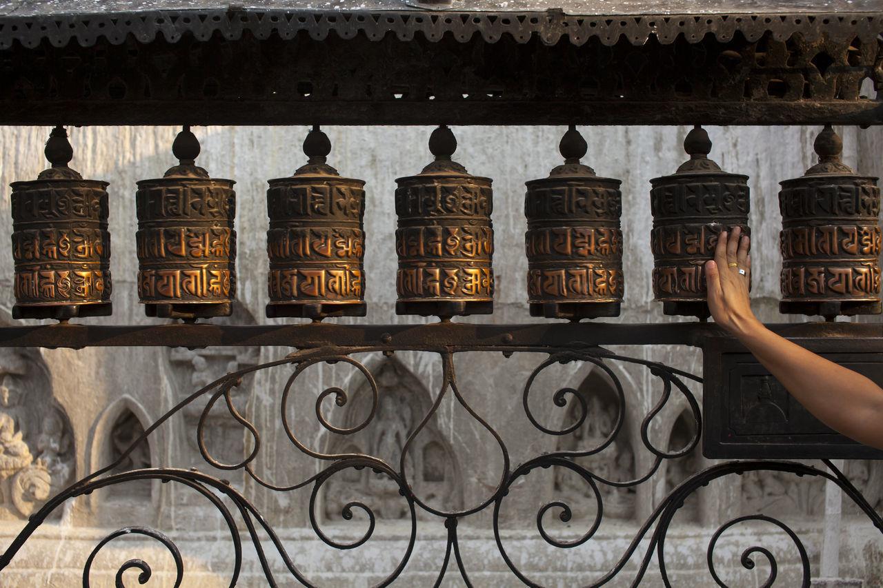 Tibetan prayer wheel with the mantra Om Mani Padme Hum written in Sanskrit on the outside of the wheel. Belief Bless Buddhism Devotee Devotion Human Hand Kathmandu Mantra Monastery Nepal Peace People Prayer Flags  Religion Sanskrit Temple Tibetan  Wheel