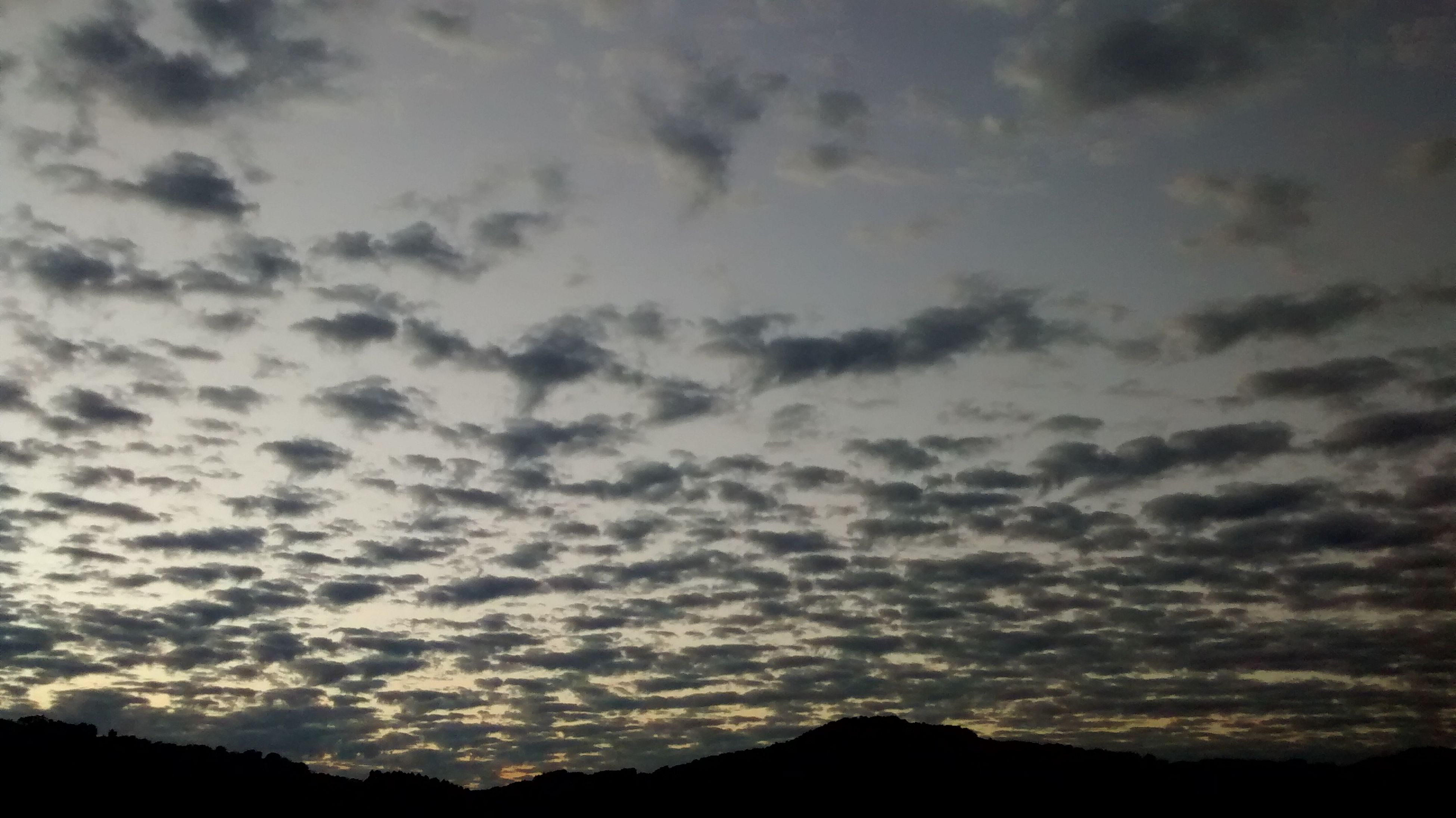 sky, silhouette, scenics, cloud - sky, tranquil scene, beauty in nature, tranquility, mountain, cloudy, nature, low angle view, cloud, sunset, idyllic, landscape, weather, dusk, cloudscape, mountain range, outdoors