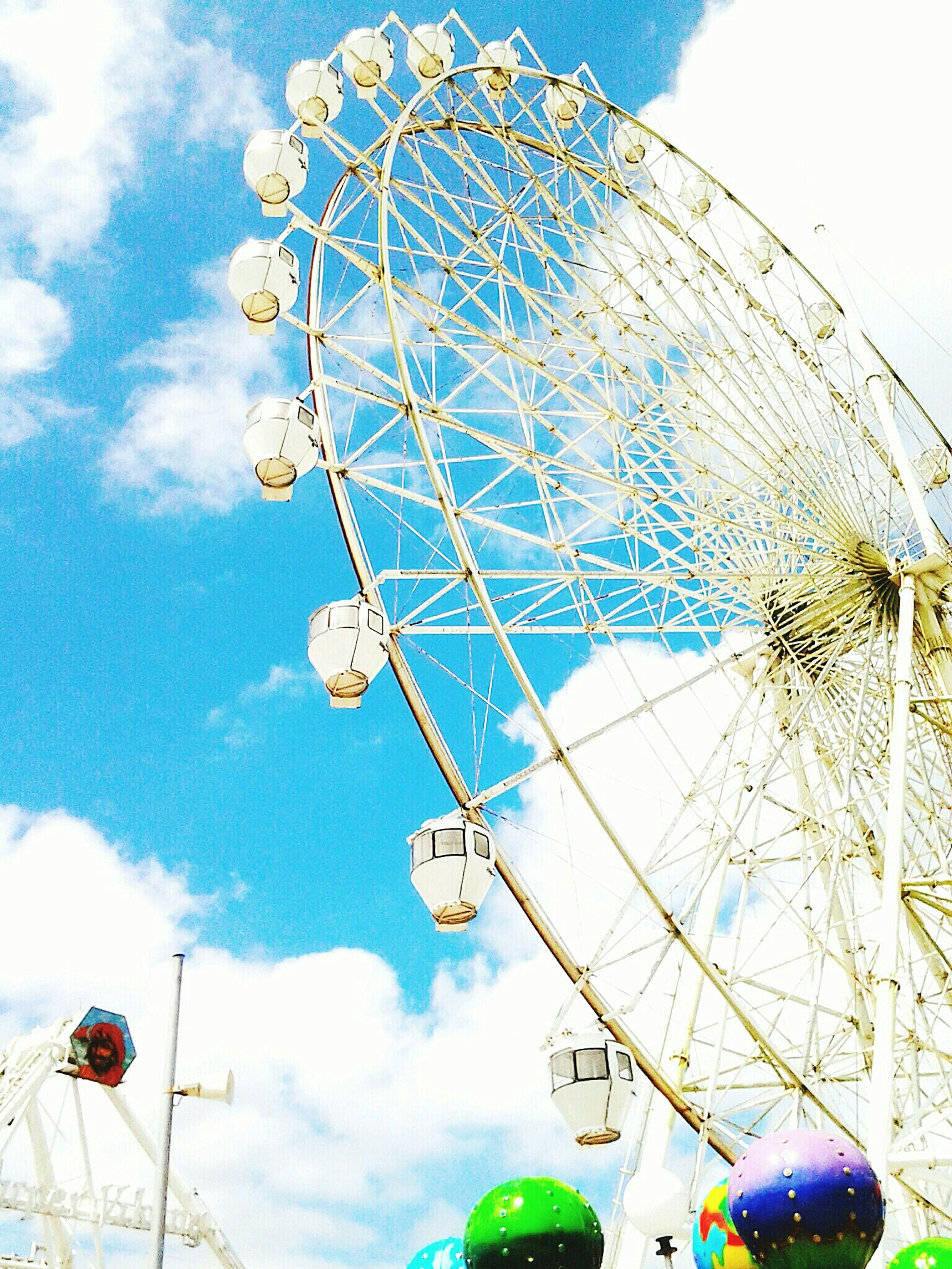 low angle view, amusement park, amusement park ride, ferris wheel, sky, arts culture and entertainment, cloud - sky, blue, fun, day, cloud, tall - high, lighting equipment, outdoors, street light, no people, metal, enjoyment, built structure, tree