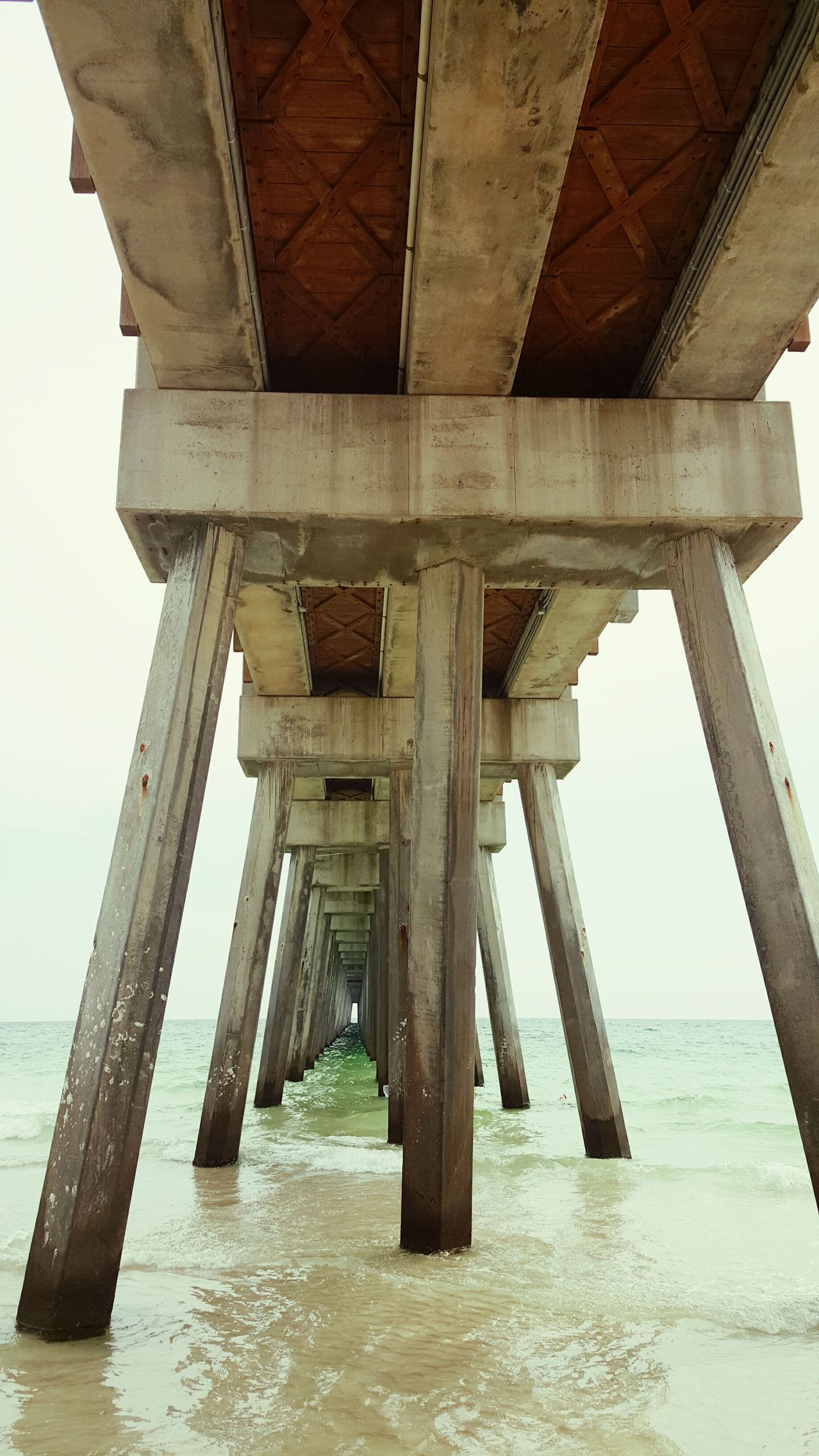 sea, water, built structure, architecture, architectural column, connection, column, pier, low angle view, support, bridge - man made structure, horizon over water, sky, engineering, bridge, tranquility, below, day, nature, clear sky