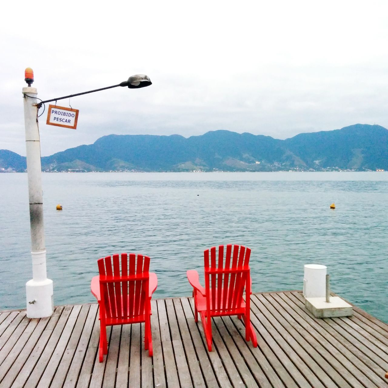 Empty Chairs Overlooking Calm Lake