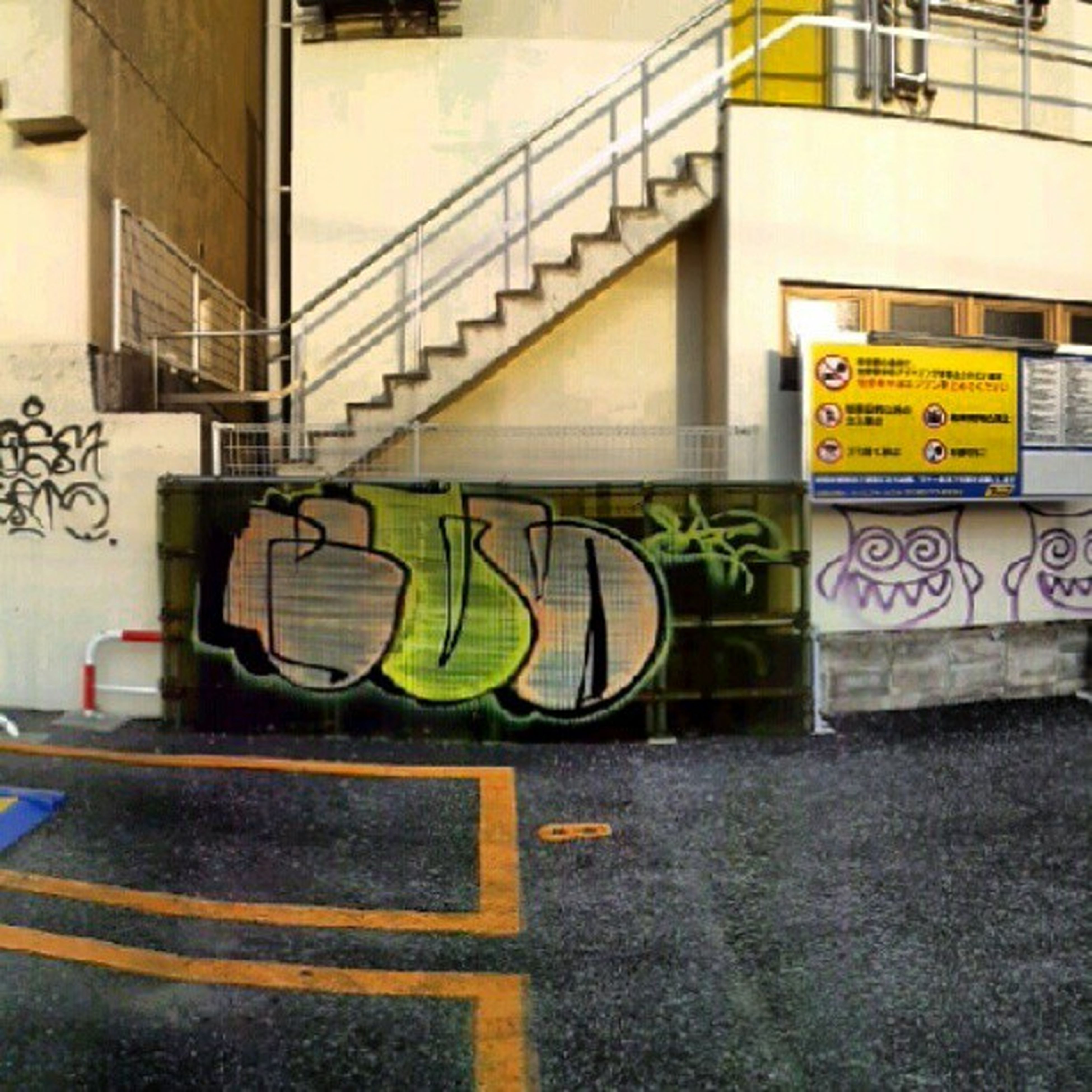 architecture, built structure, building exterior, yellow, text, wall - building feature, graffiti, railing, western script, transportation, building, street, day, city, no people, sunlight, communication, outdoors, wall, steps
