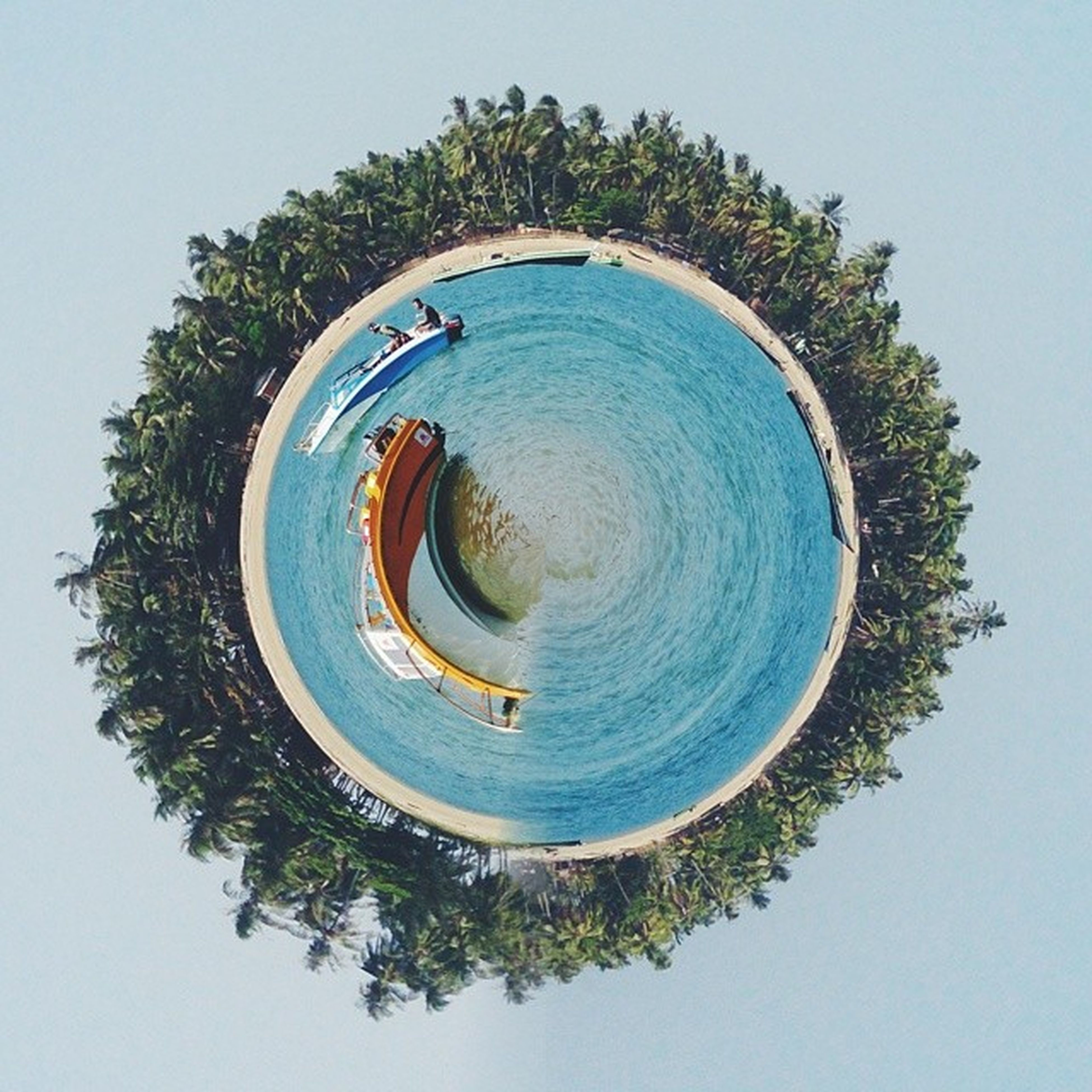 circle, blue, high angle view, clear sky, geometric shape, tree, day, directly above, no people, low angle view, outdoors, copy space, shape, nature, water, reflection, round, spiral, built structure, fish-eye lens