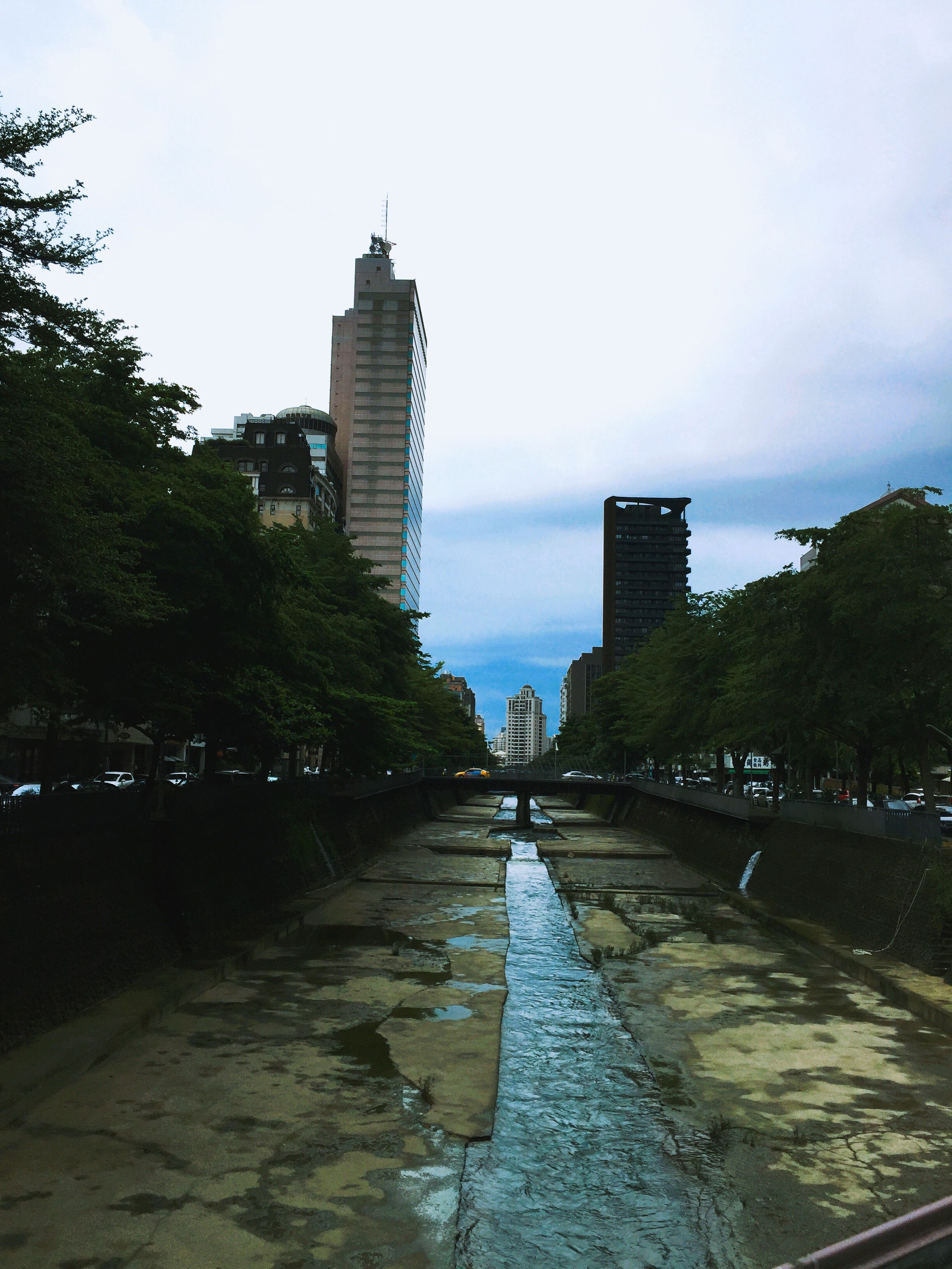 architecture, building exterior, skyscraper, built structure, city, sky, tree, tower, water, reflection, modern, river, outdoors, cityscape, growth, travel destinations, no people, urban skyline, day, nature