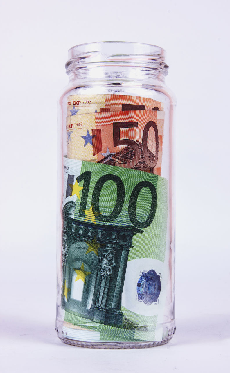 Close-Up Of Paper Currency In Glass Jar Against White Background