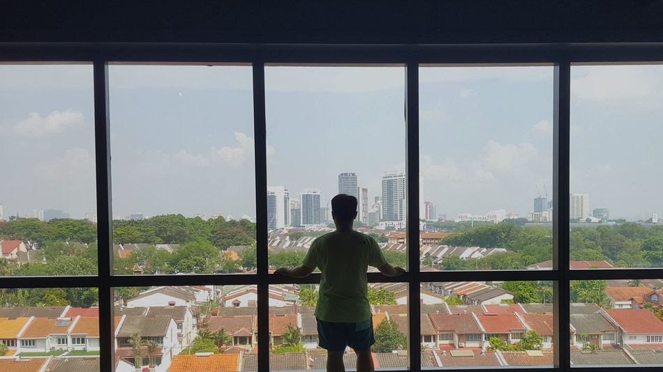 A cityscape. A view to behold Window Looking Through Window Indoors  Cityscape City Skyscraper One Person People Office Adult Standing Sky Adults Only Business Only Women Day Architecture Asian Guy One Woman Only Young Adult Loneliness Lonelyplanet Architectureporn EyeEm Selects Malaysia EyeEmNewHere Your Ticket To Europe The Week On EyeEm Done That. Lost In The Landscape Connected By Travel