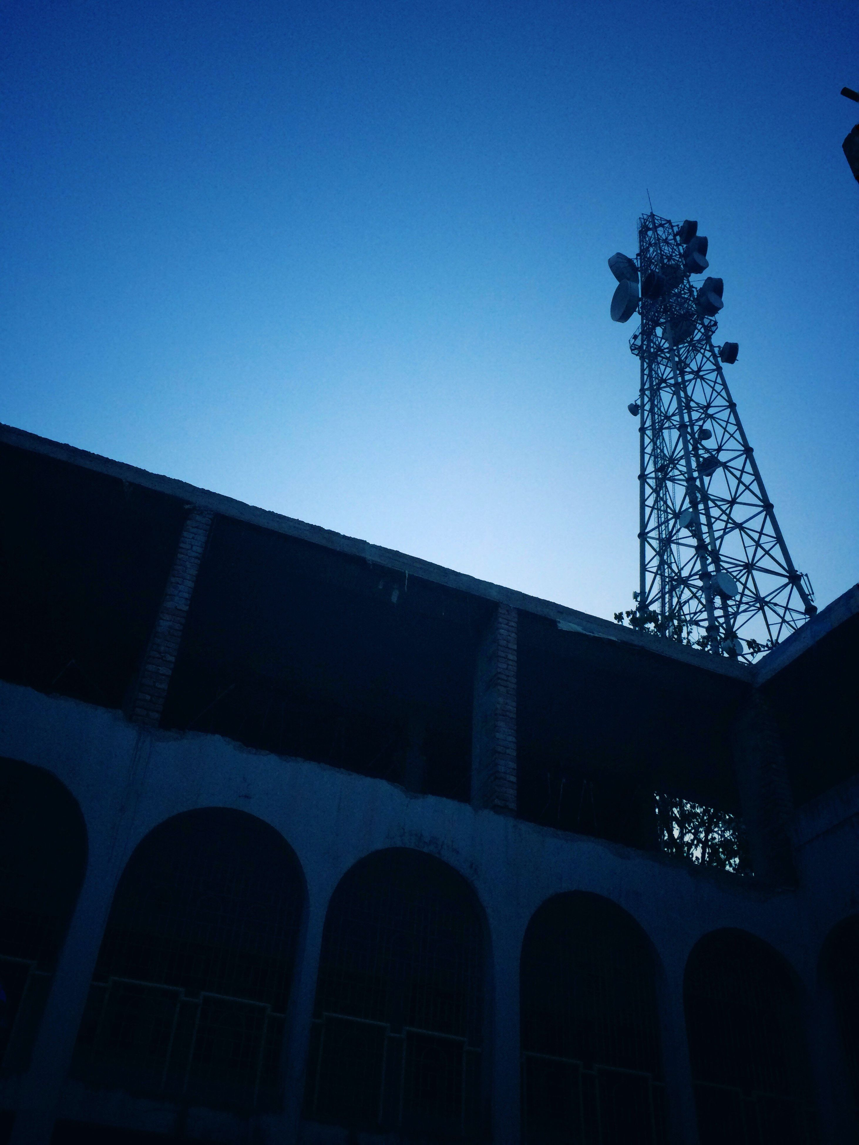 low angle view, clear sky, built structure, architecture, building exterior, blue, copy space, outdoors, building, no people, day, city, sky, tree, high section, connection, street light, communication, dusk