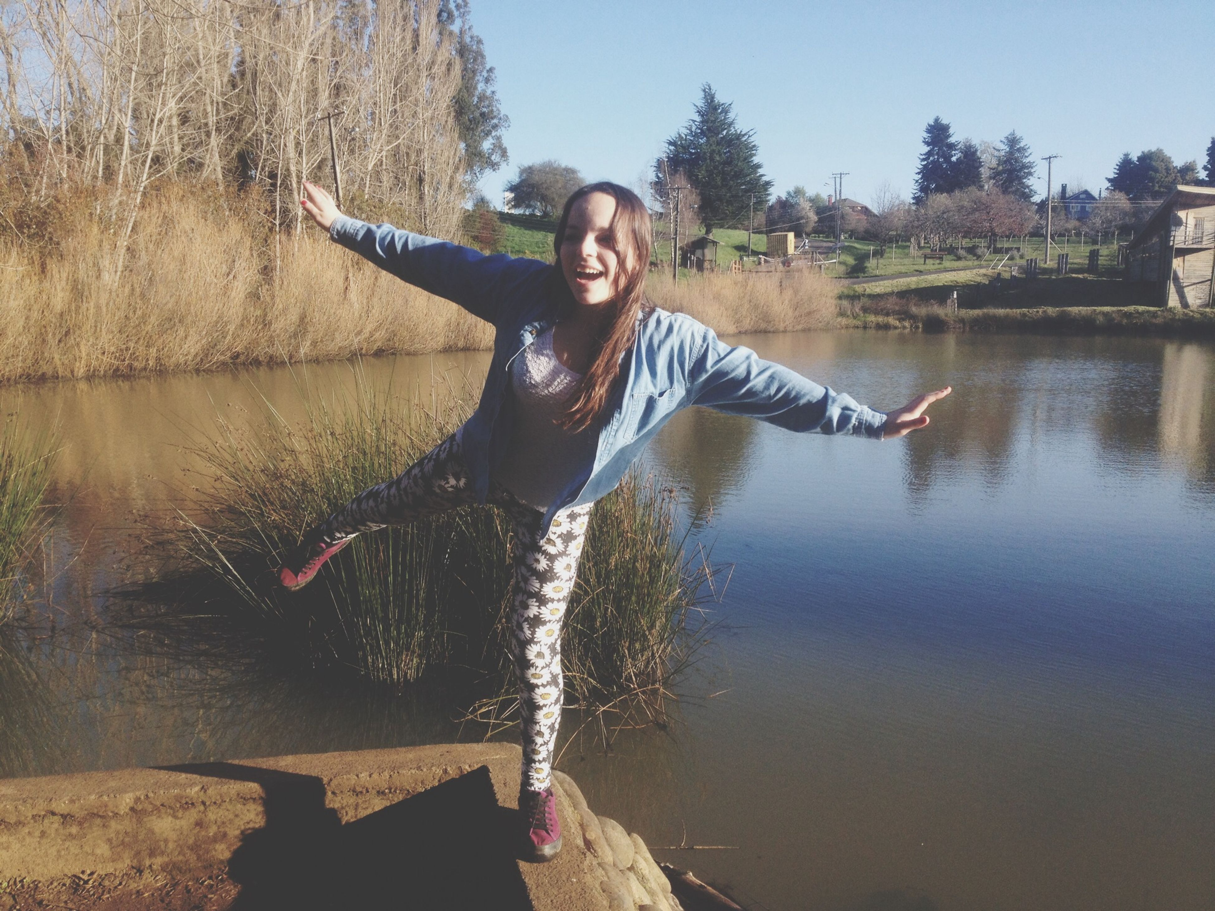 person, young adult, looking at camera, casual clothing, full length, lifestyles, portrait, water, leisure activity, front view, smiling, young women, standing, happiness, three quarter length, sitting, river