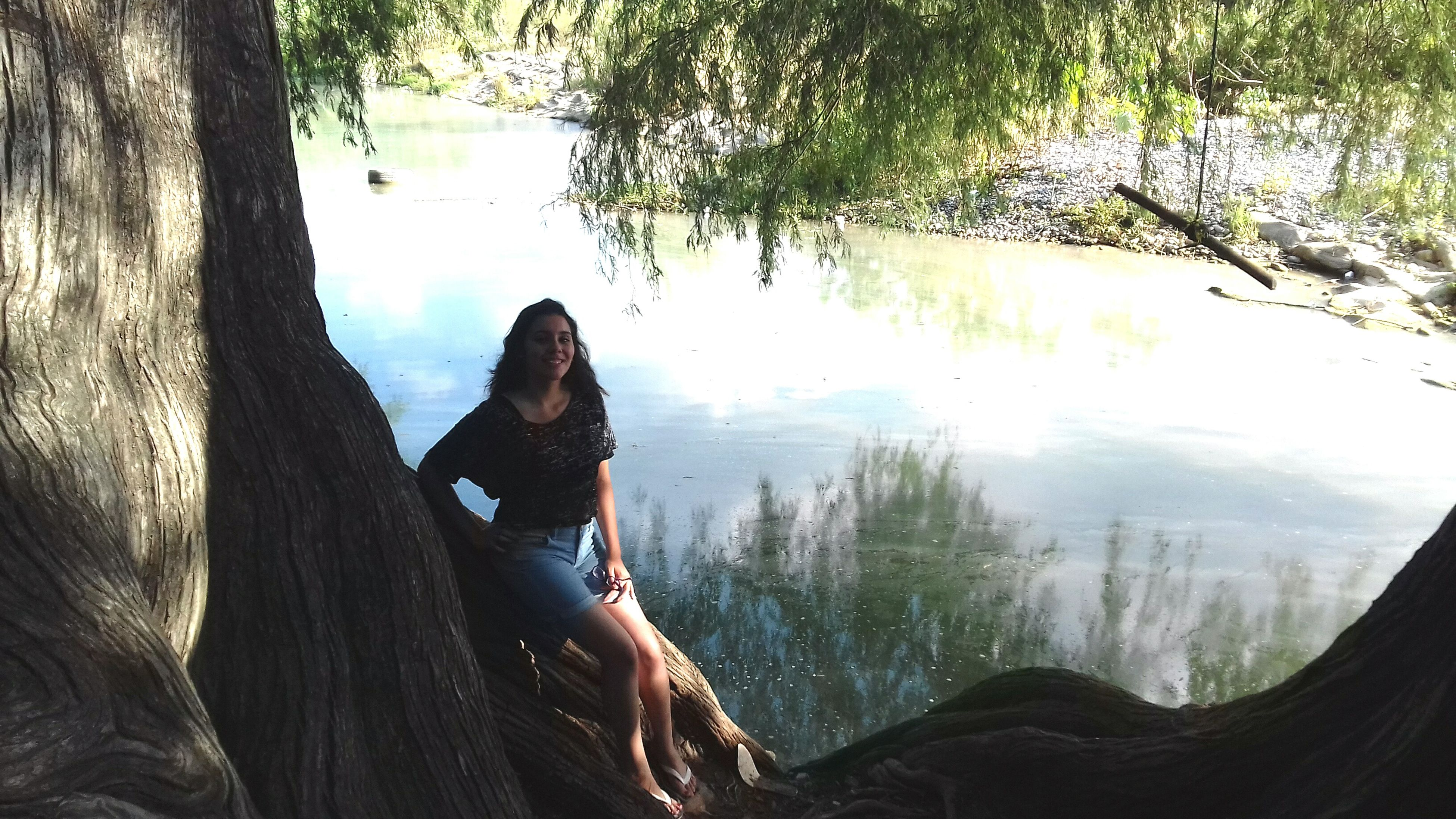 tree, one person, nature, real people, leisure activity, tree trunk, day, beauty in nature, water, young adult, young women, tranquility, lifestyles, full length, tranquil scene, outdoors, sitting, scenics, relaxation, standing, women, beautiful woman, people