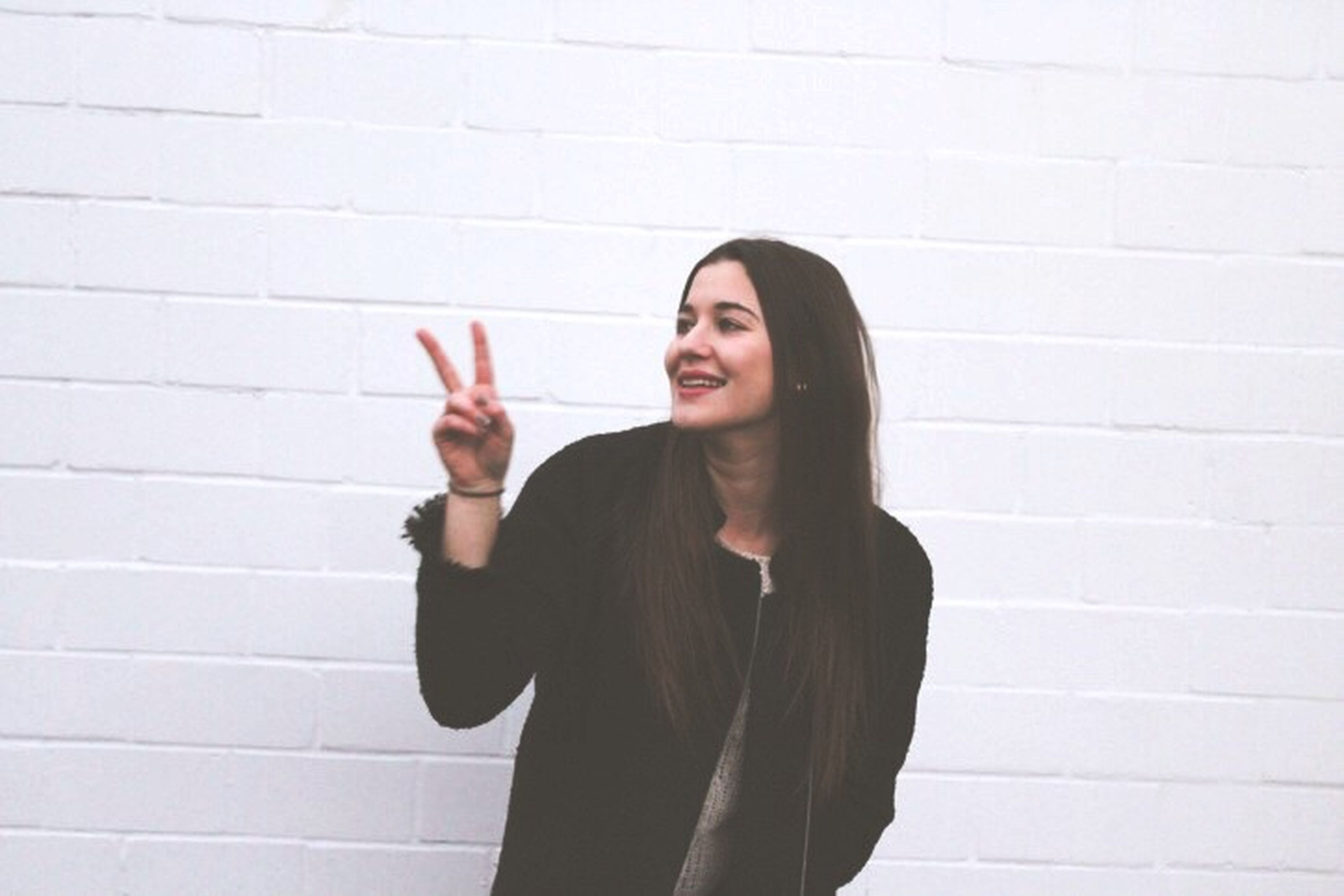 gesturing, smiling, waist up, only women, one person, one woman only, adults only, long hair, communication, portrait, business, well-dressed, young adult, women, people, human body part, thumbs up, cheerful, happiness, adult, human hand, outdoors, day, one young woman only, young women